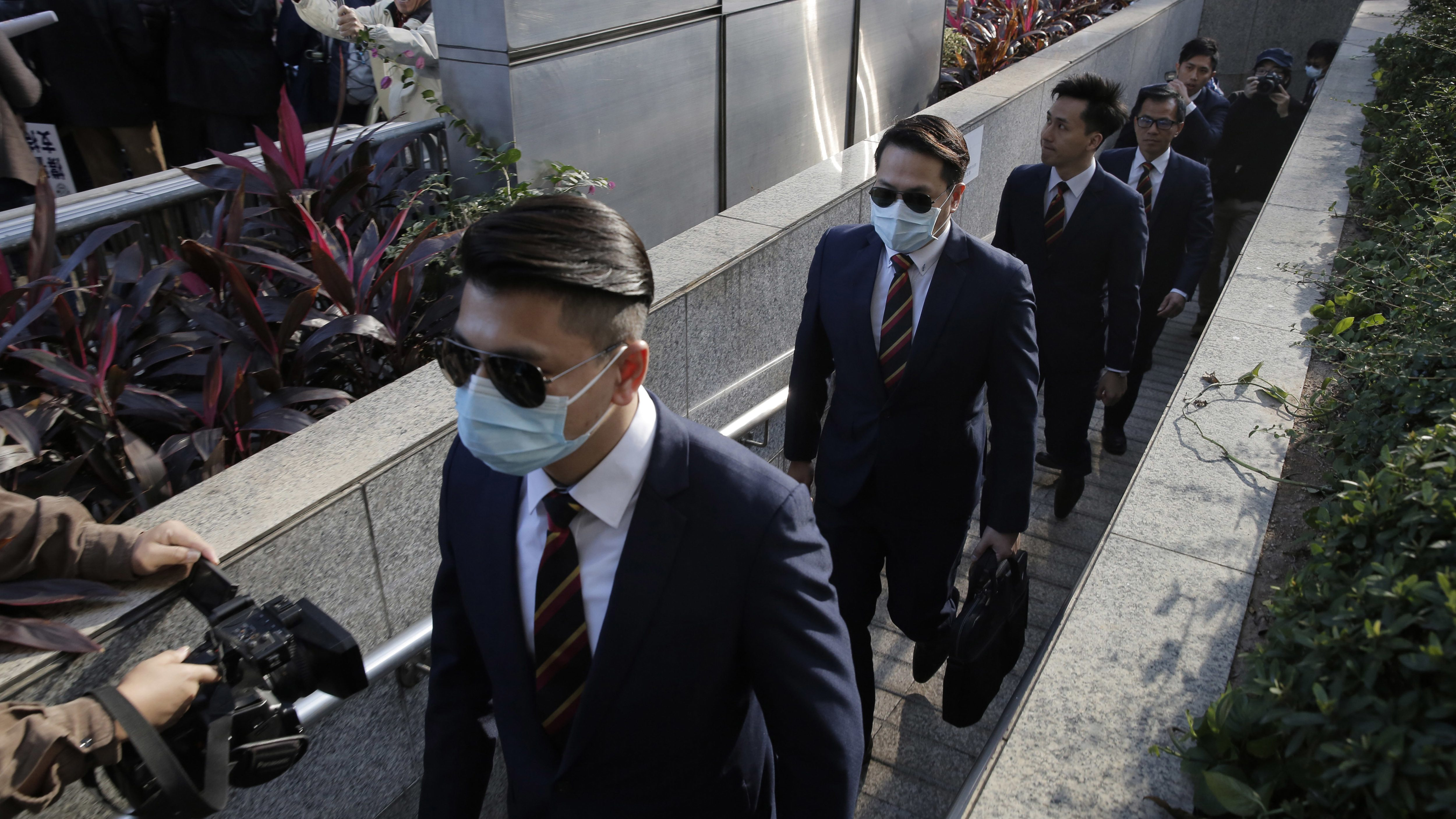 Five of the seven Hong Kong police officers, from left, Police Constable Wong Wai-ho, Police Constable Lau Hing-pui, Senior Inspector Lau Cheuk-ngai, Sergeant Pak Wing-bun and Police Constable Kwan Ka-ho arrive the District Court in Hong Kong Tuesday, Feb. 14, 2017 as they were charged with assaulting a pro-democracy activist in an incident on Oct. 15 2014. Seven Hong Kong police officers have been found guilty of a lesser charge in the assault of a pro-democracy activist whose videotaped beating during the height of 2014 pro-democracy protests sparked outrage. A district court judge found the seven officers guilty of one joint count of assault occasioning actual bodily harm on Tuesday.