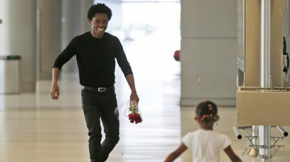 Olympic silver medalist Feyisa Lilesa, left, of Ethiopia, runs to meet his daughter Soko, 5, while picking up his family at Miami International Airport, Tuesday, Feb. 14, 2017, in Miami. Lilesa arrived in the U.S. on a special skills visa, which allows him to train and compete until January. His wife, son, daughter and brother joined him in Miami Tuesday.