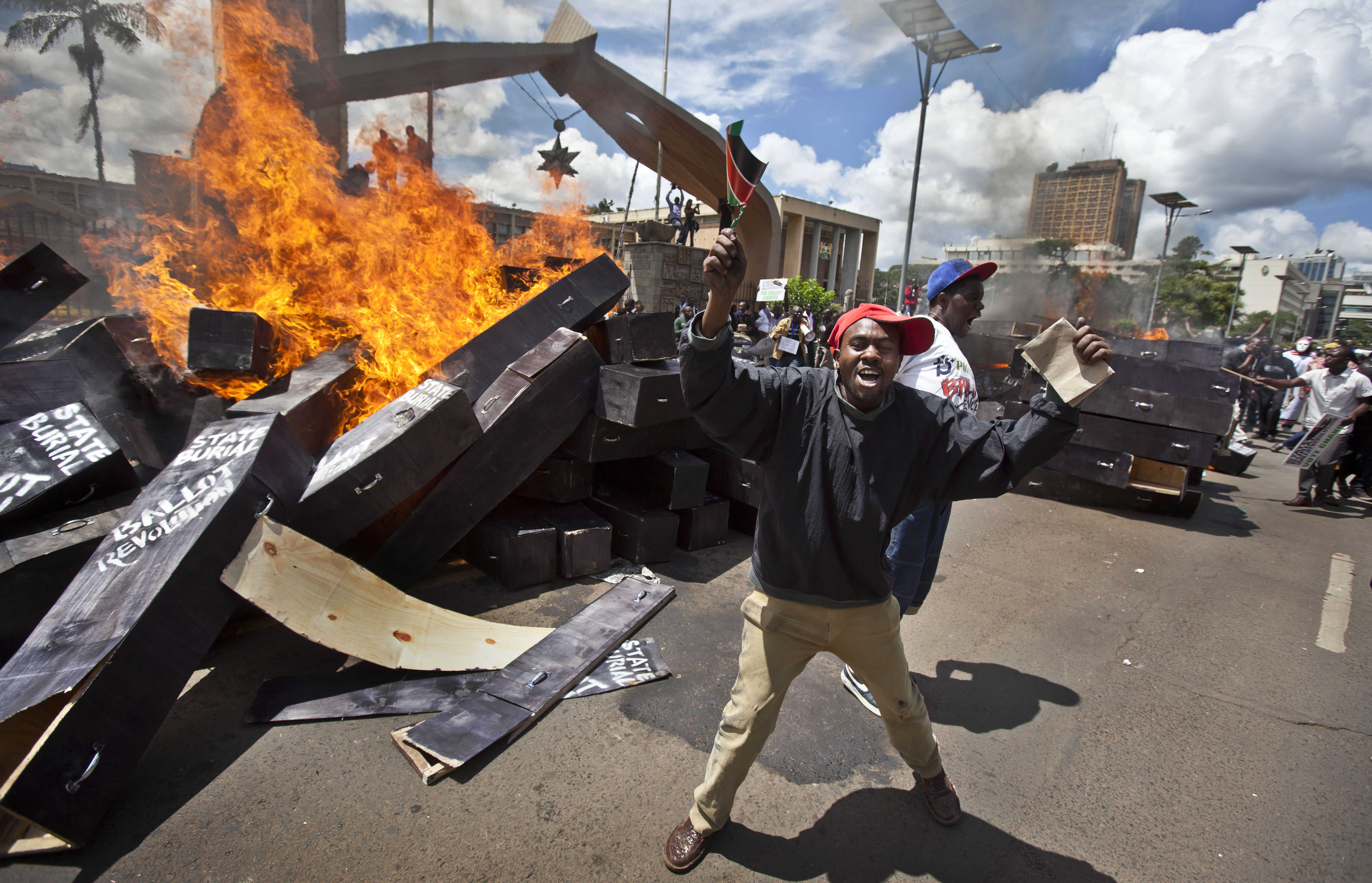 """FILE - In this Wednesday, Jan. 16, 2013 file photo, a demonstrator celebrates after setting fire to mock coffins on which were written """"State Burial, Ballot Revolution"""" outside the Parliament in Nairobi, Kenya. The protest was organized by social campainger Boniface Mwangi over a pay increase for members of parliament."""