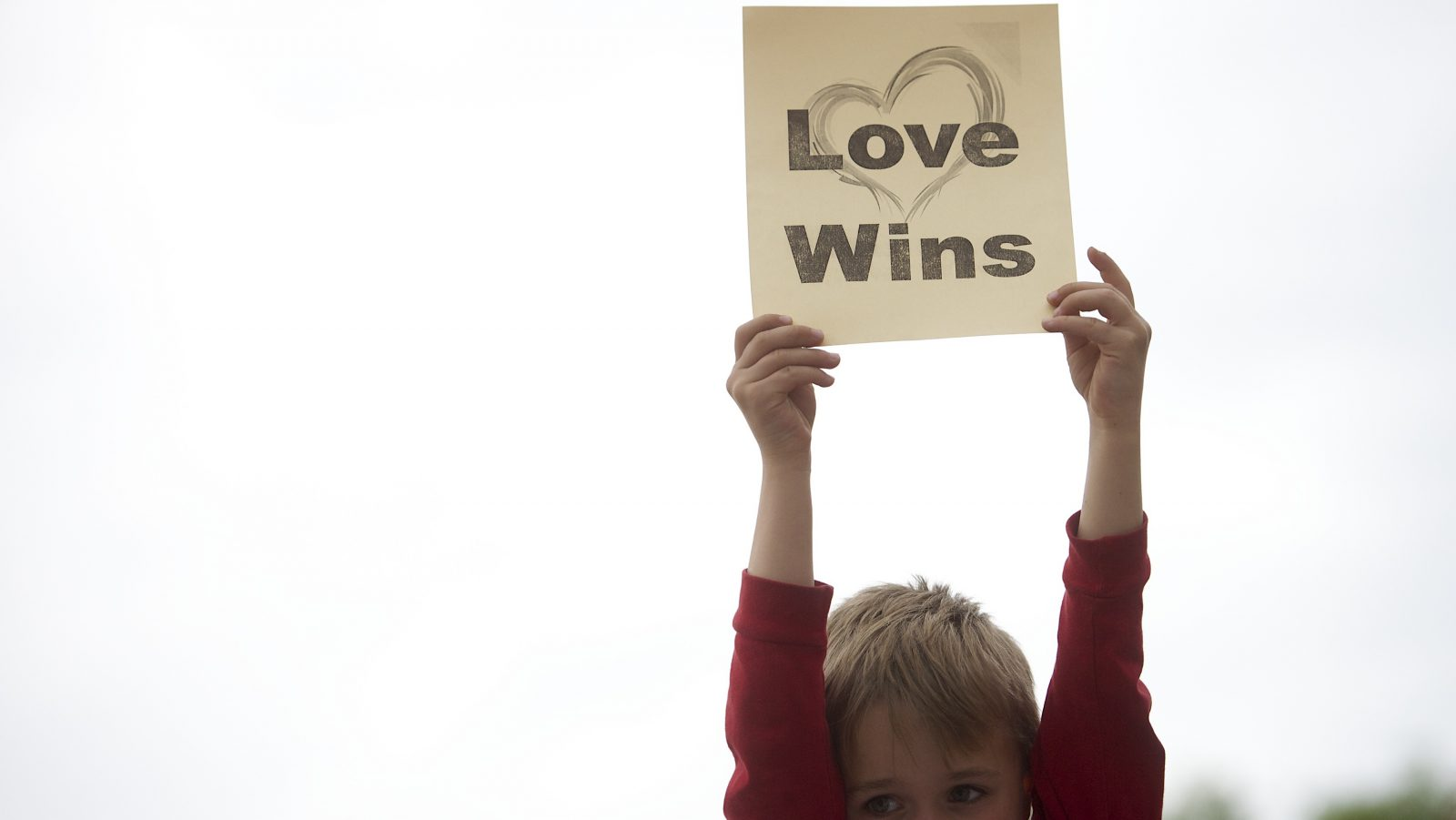 A boy holds up a sign during a rally by gay rights supporters.