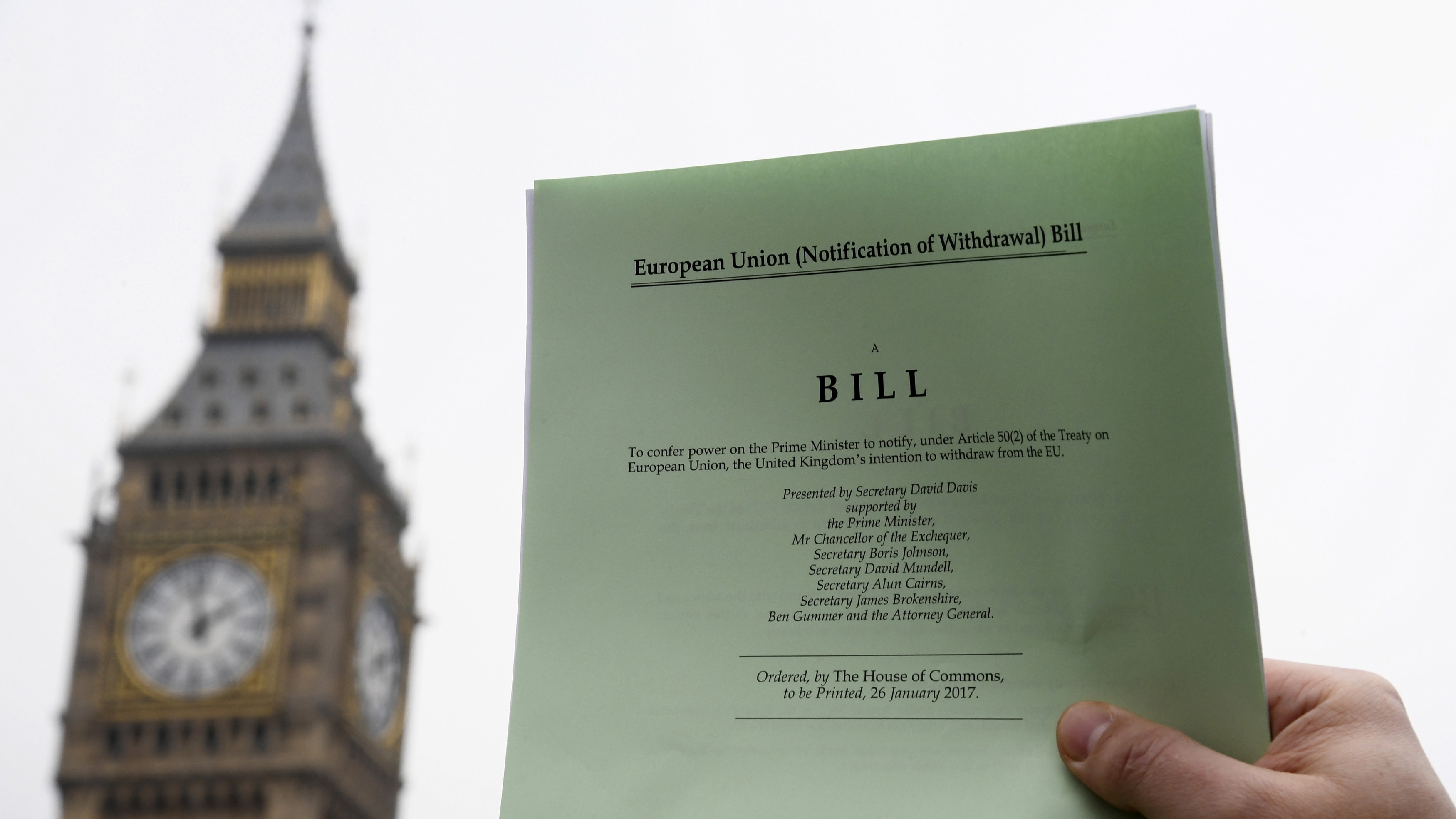 A journalist poses with a copy of the Brexit Article 50  bill, introduced by the government to seek parliamentary approval to start the process of leaving the European Union, in front of the Houses of Parliament in London, Britain, January 26, 2017. REUTERS/Toby Melville - RTSXHHR