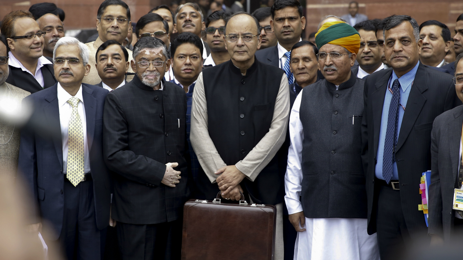 Indian Finance Minister Arun Jaitley, center, holding a briefcase containing federal budget documents leaves his office to present the same in Parliament in New Delhi, India, Wednesday, Feb. 1, 2017.