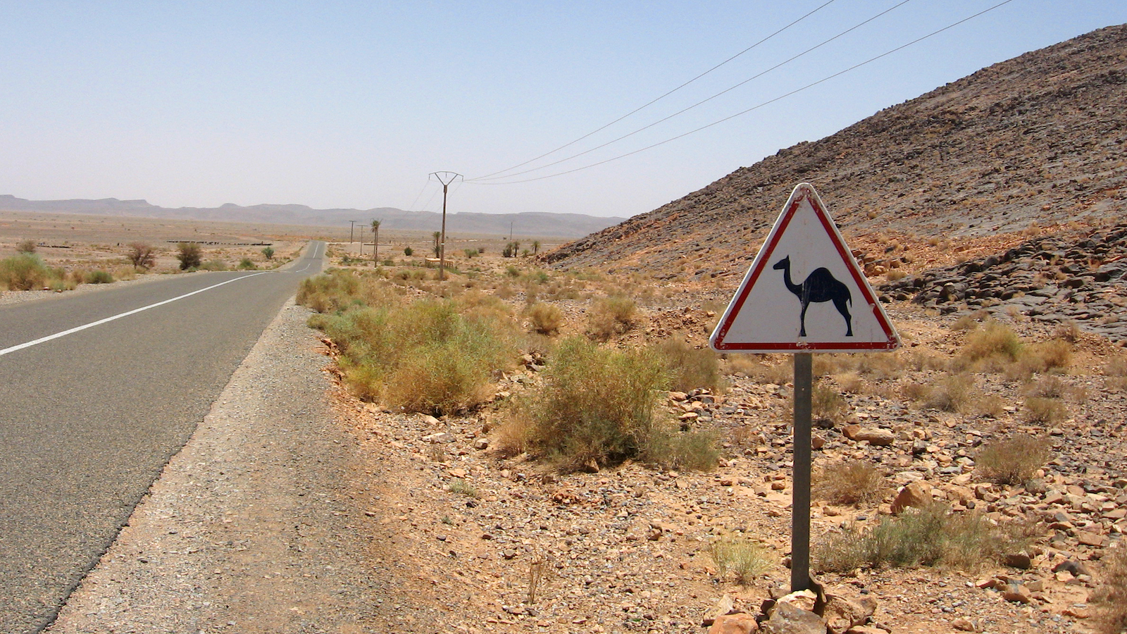FILE - This June 2013 file photo shows a sign indicating a camel crossing on the road to Erfoud, Morocco, a town on the edge of the Sahara desert. A three-day loop from Marrakech to the dunes of Erg Chebbi by camel and air-conditioned SUV offers a look at one of Africa's most mythic and historic trading routes - the road to Timbuktu. (AP Photo/Giovanna Dell'Orto, File)