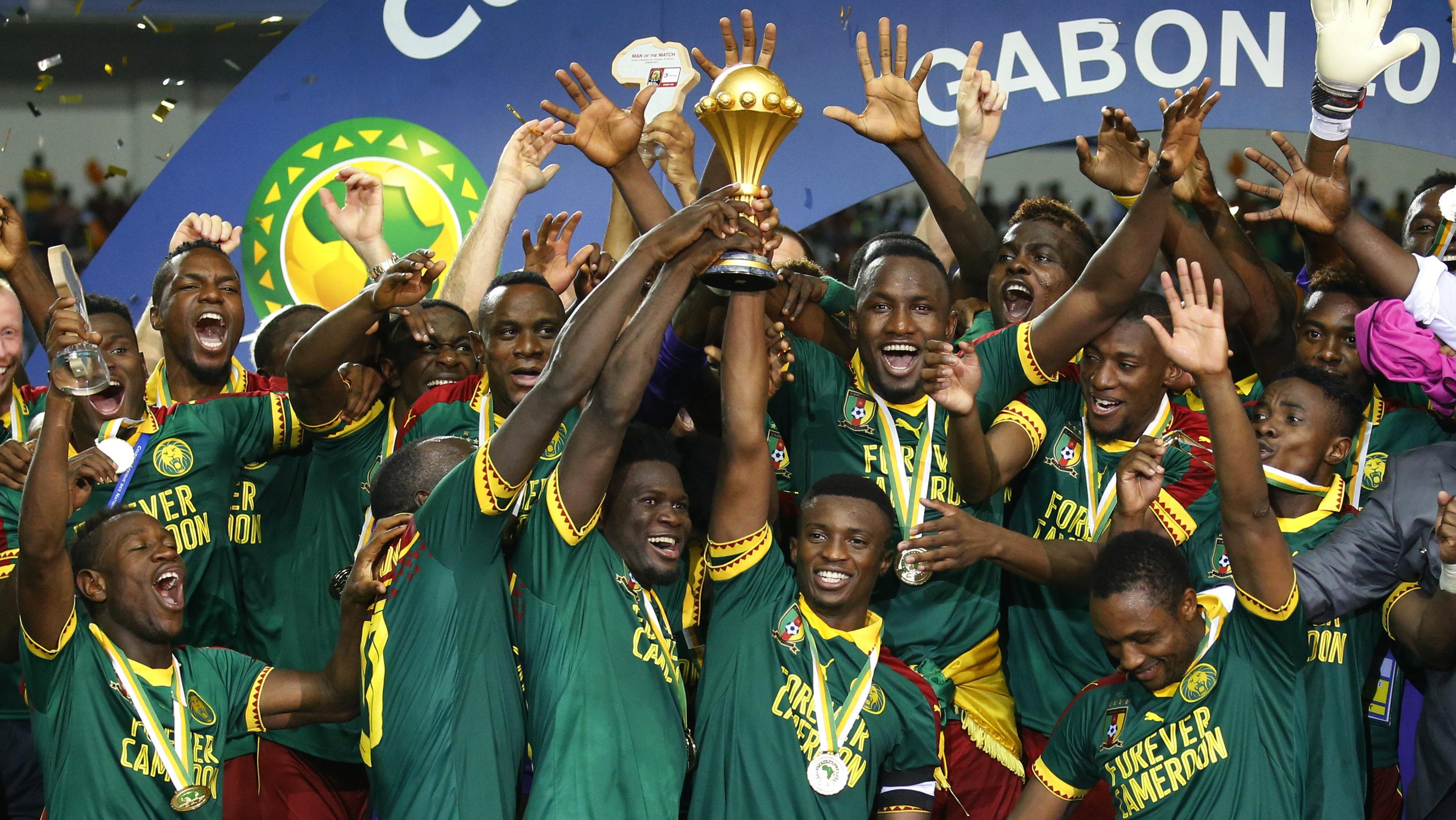 Cameroon's Benjamin Moukandjo celebrates with the trophy and teammates