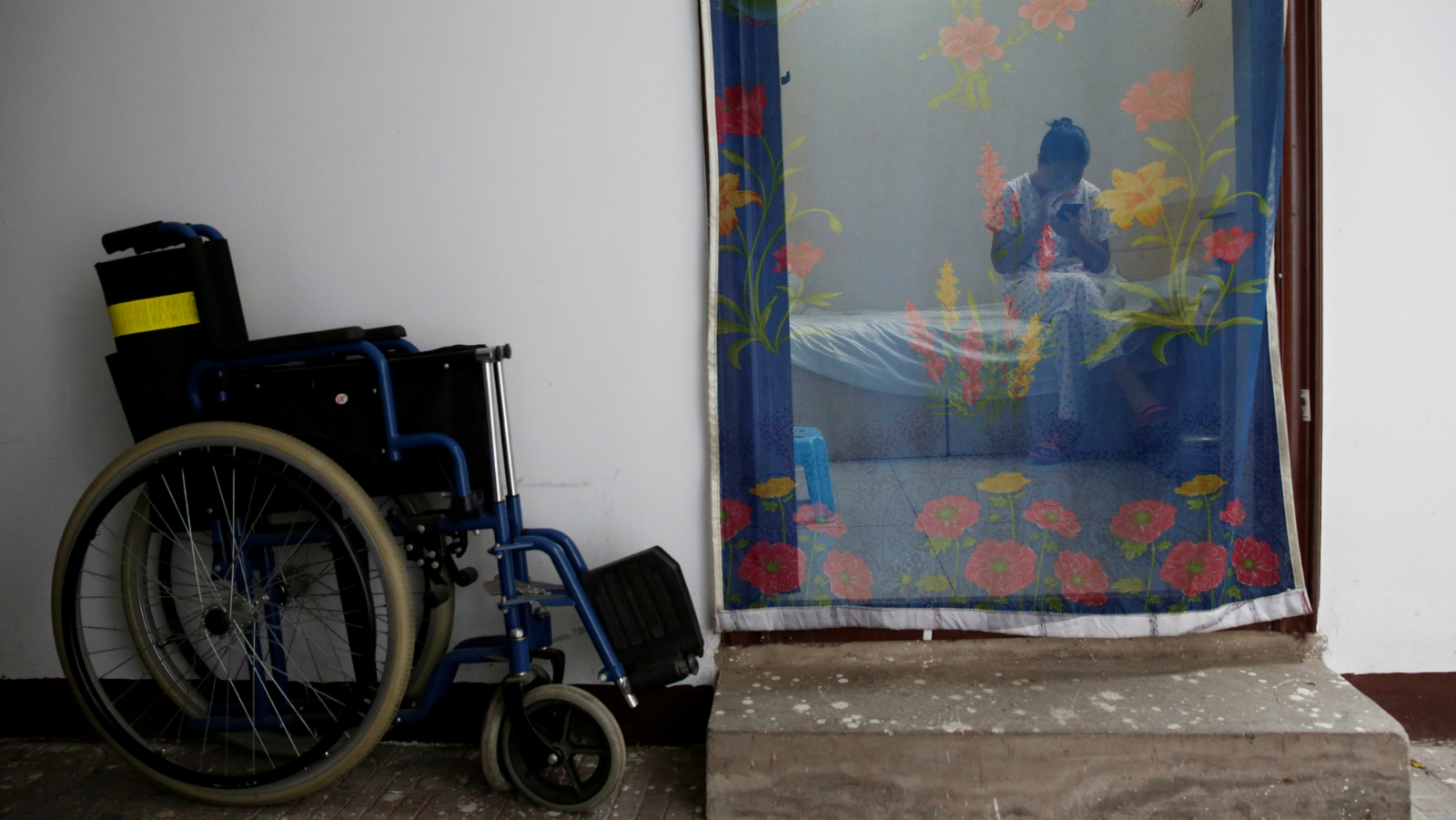 DATE IMPORTED:September 29, 2016Wang uses a mobile phone as she take a rest in her room at the accommodation where patients and their family members stay while seeking medical treatments in Beijing, China, June 23, 2016. Wang, who suffers from cervical cancer, came from Inner Mongolia to seek treatment at a specialist hospital in Beijing.