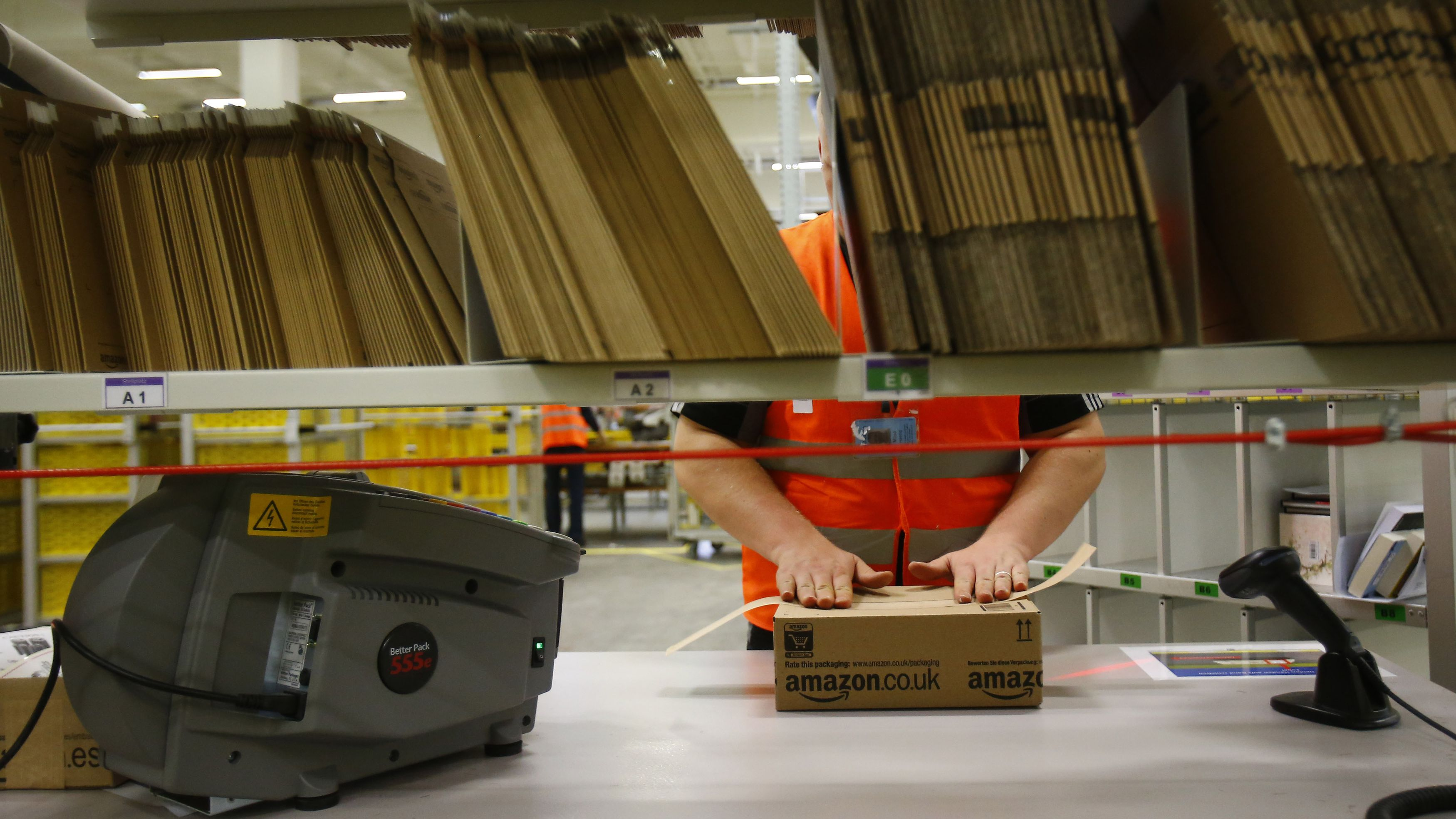"A worker handles items for delivery at Amazon's new distribution center in Brieselang, near Berlin November 28, 2013. Germany's antitrust watchdog has dropped an investigation into Amazon after the world's biggest Internet retailer agreed to stop forcing third-party merchants to offer their cheapest price when selling products on its platform. Andreas Mundt, the president of the German cartel office, said it had decided to set aside the case against Amazon after the company agreed to cancel that demand from the terms and conditions of its contracts with merchants. ""Making pricing demands to your own competitors cannot be justified in any circumstances, not even with the undeniable advantages of an online market place."" REUTERS/Tobias Schwarz (GERMANY - Tags: BUSINESS EMPLOYMENT)"