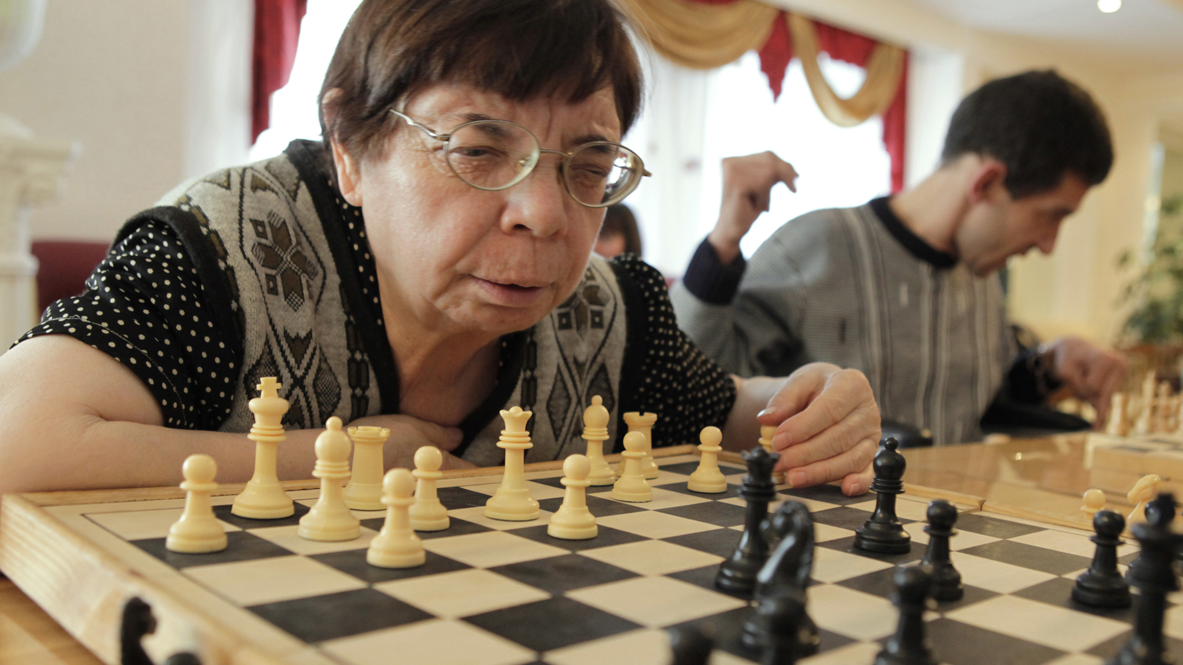 An elderly woman takes part in a chess competition at a gerontological center in Stavropol November 25, 2010. Some 40 participants from elderly homes around the region took part in the competition.  REUTERS/Eduard Korniyenko  (RUSSIA - Tags: SPORT CHESS HEALTH SOCIETY IMAGES OF THE DAY) - RTXV257