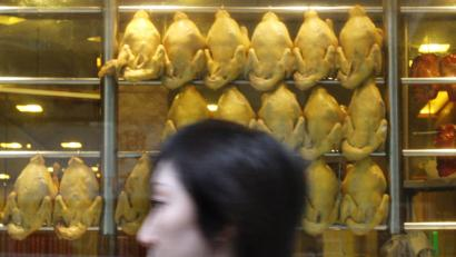 A woman walks past some cooked chickens outside a restaurant in Hong Kong on Thursday, June 12, 2008, one day after health officials ordered the slaughter of all live poultry in Hong Kong's street markets on Wednesday after detecting one of the largest outbreaks of the bird flu virus in years. (AP Photo/Vincent Yu)