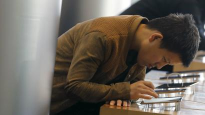 A man tries Apple's iPhone 6 at an apple store in Beijing