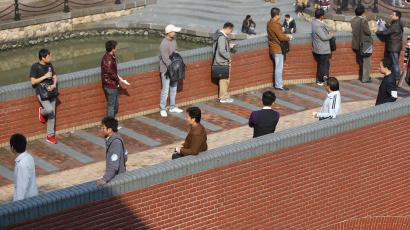 Men wait for women on a bridge during a blind date party in Shanghai November 12, 2011. The blind date party was held a day after November 11, 2011, or Super Bachelors Day which has six 1s in the date. The event, aimed at providing chances for the unmarried under the age of 35, has attracted about 10,000 single young people to participate, local media reported. REUTERS/Aly Song (CHINA - Tags: SOCIETY) - RTR2TX11