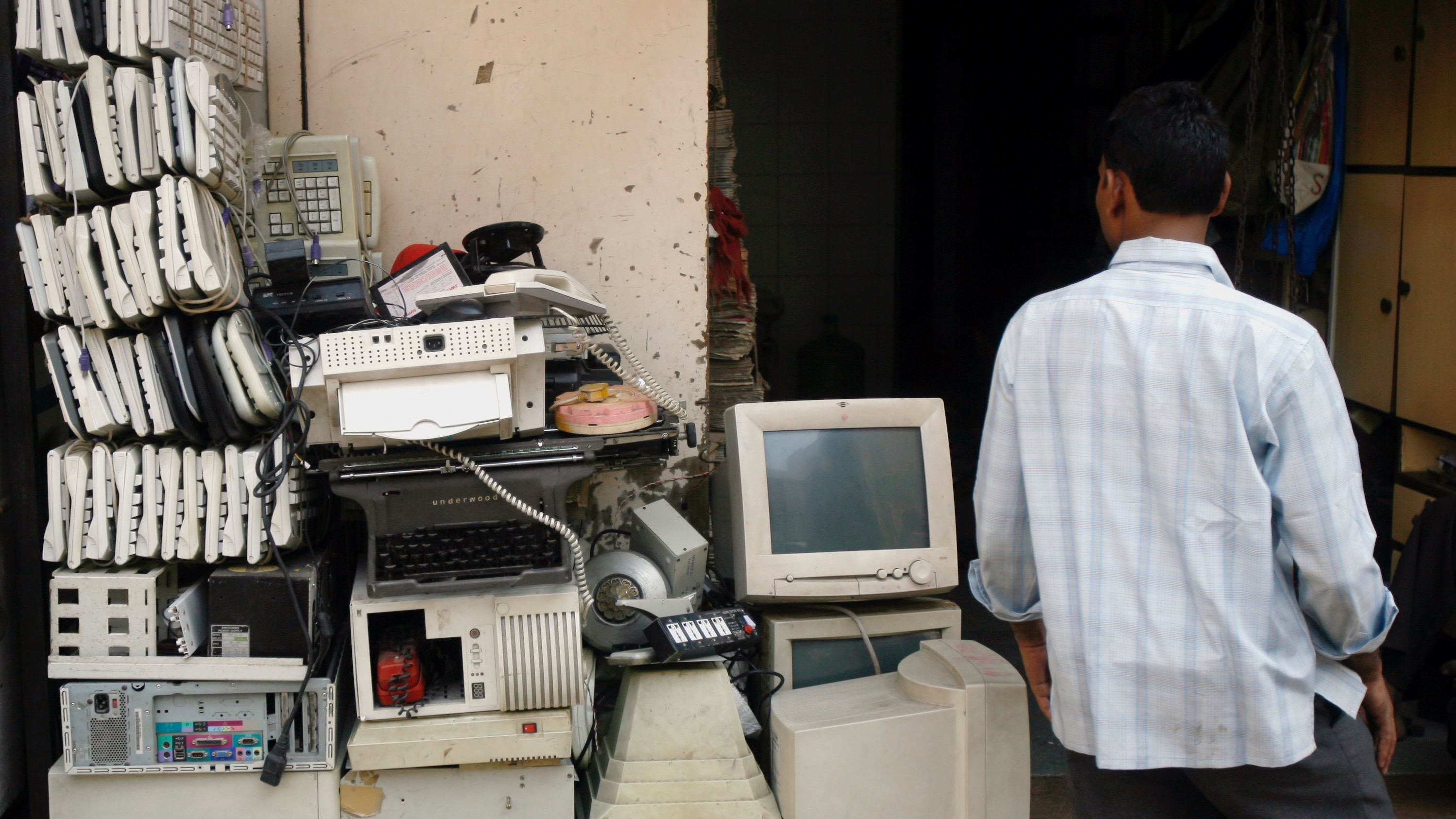 A man walks past electronic waste, also known as e-waste, at a junk shop in Mumbai October 27, 2008. REUTERS/Arko Datta (INDIA) - RTX9YMM