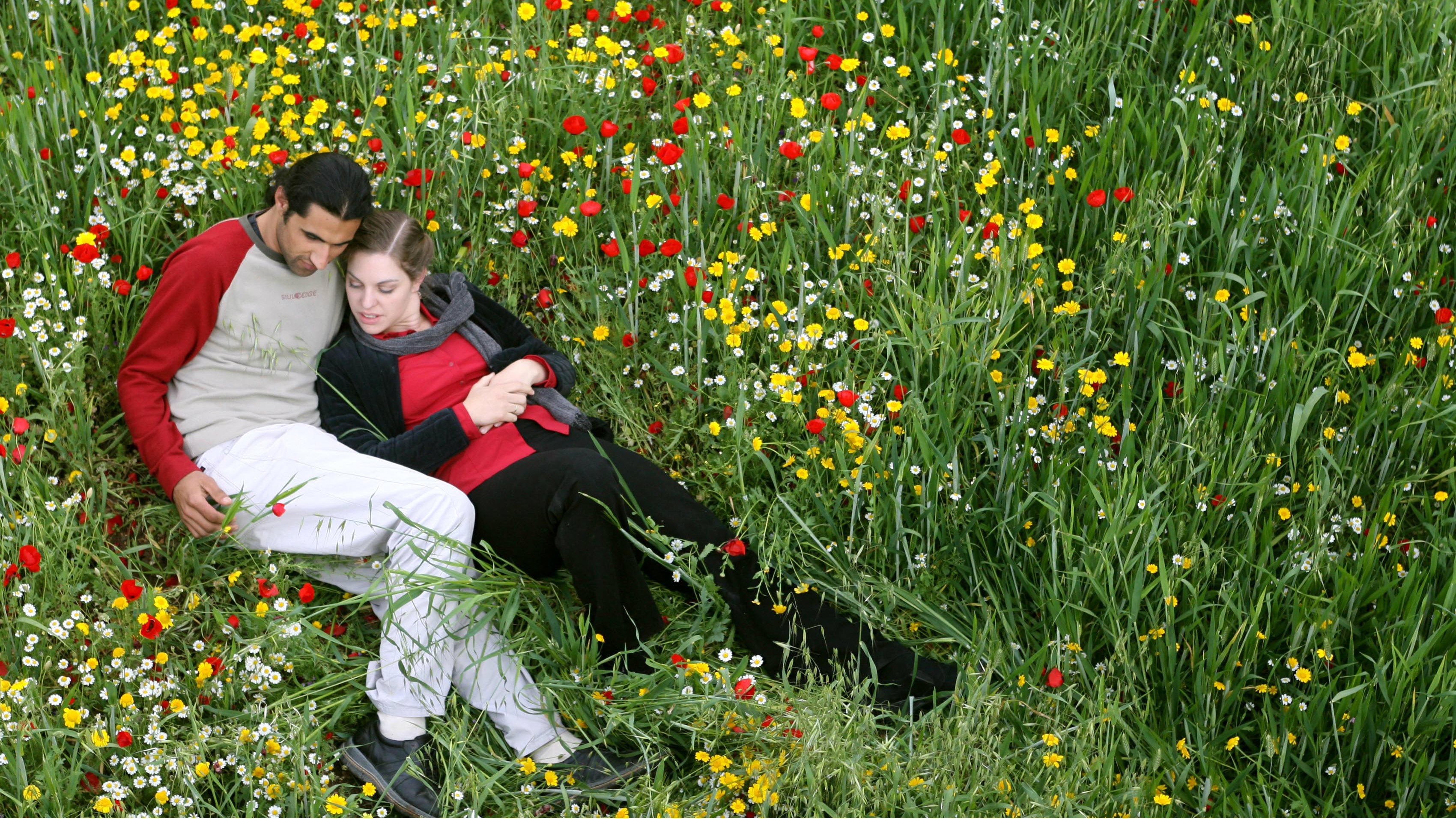 """Palestinian Muslim Osama Zatar, 26, spends some quiet time with his Israeli Jew wife, Jasmin Avissar, 25, near the West Bank village of Qarawat Bani Zeid near Ramallah, April 10, 2006. The couple's """"Romeo and Juliet"""" struggle to live together is a rare tale of cross-border love in a land riven by years of violence between Israel and Palestinians. Picture taken April 10, 2006. To match feature MIDEAST-COUPLE REUTERS/Eliana Aponte"""