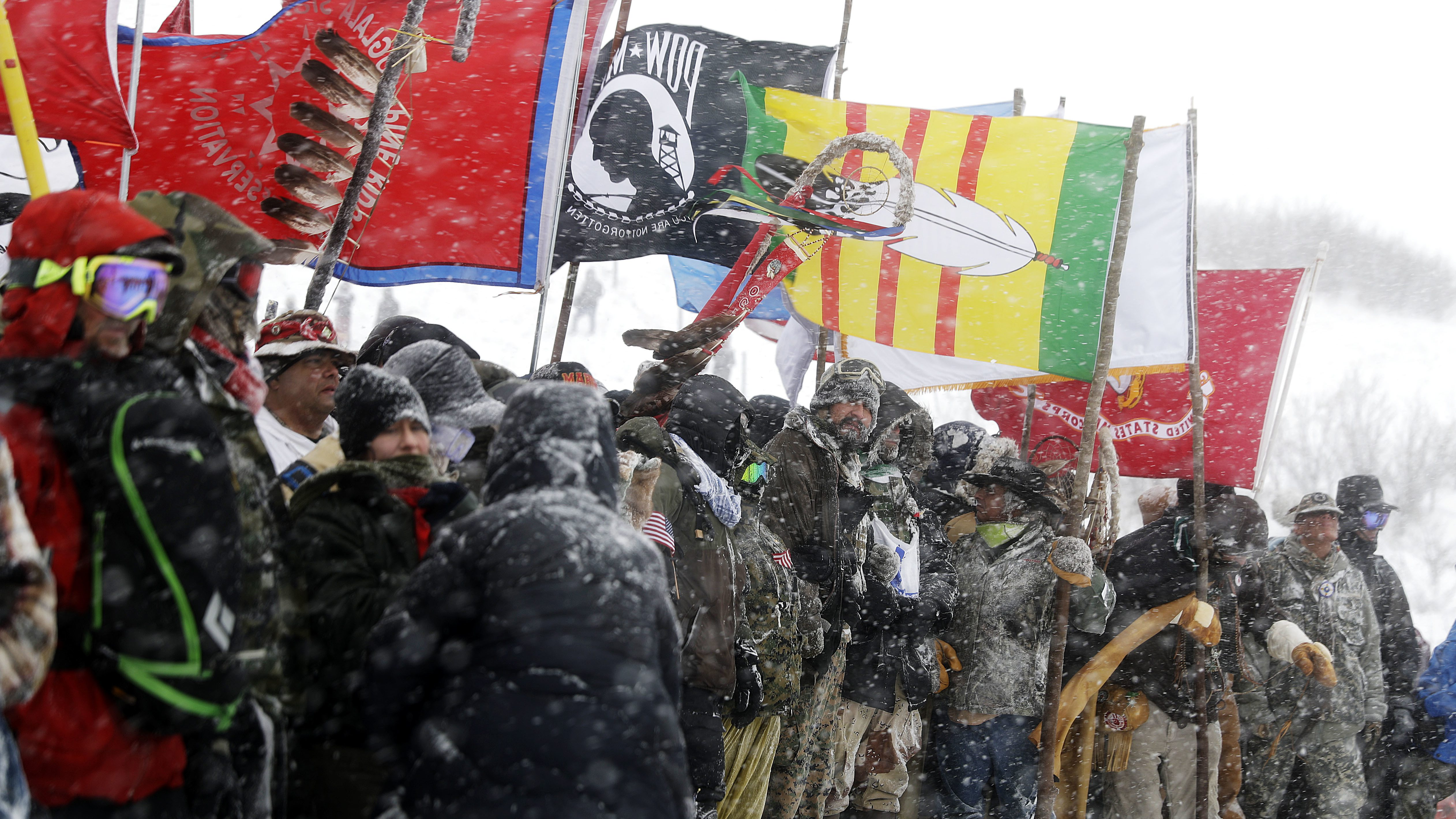 In this Dec. 5, 2016, file photo, military veterans and Native American tribal elders come to a stop for a ceremonial prayer during a march to a closed bridge across from the Dakota Access oil pipeline site in Cannon Ball, N.D. Some Native Americans worry the transition to a Donald Trump administration signals an end to eight years of sweeping Indian Country policy reforms. But Trump's Native American supporters said they're hopeful he will cut through some of the government red tape that they believe has stifled economic progress on reservations.