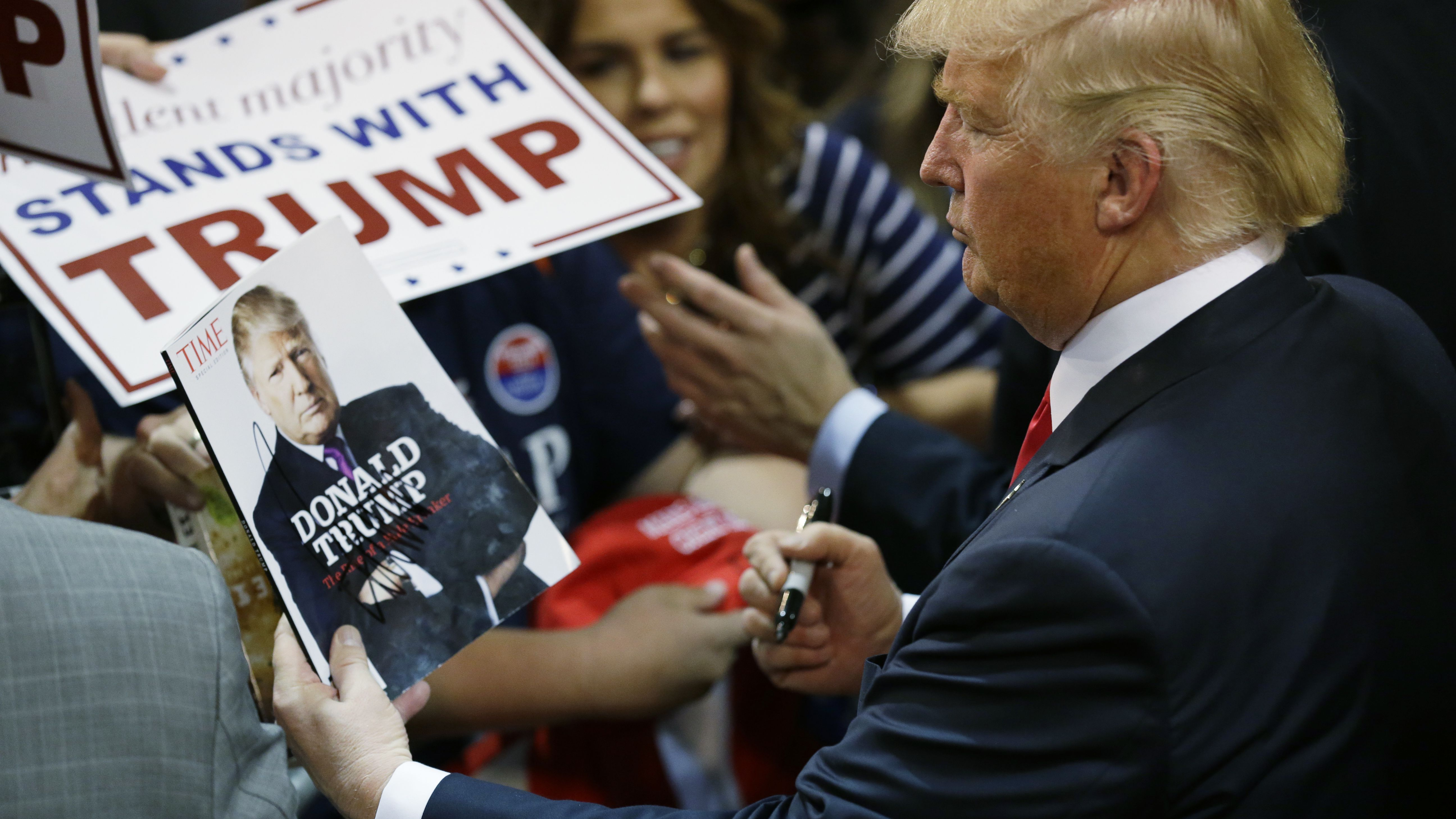 Donald Trump looks at his photo on a magazine cover as he signs autographs during a rally in Eugene, Ore. in 2016.