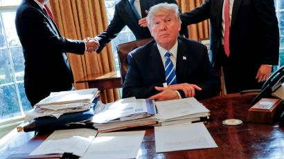 President Donald Trump sits at his desk after a meeting with Intel CEO Brian Krzanich, left, and members of his staff in the Oval Office of the White House in Washington, Wednesday, Feb. 8, 2017.