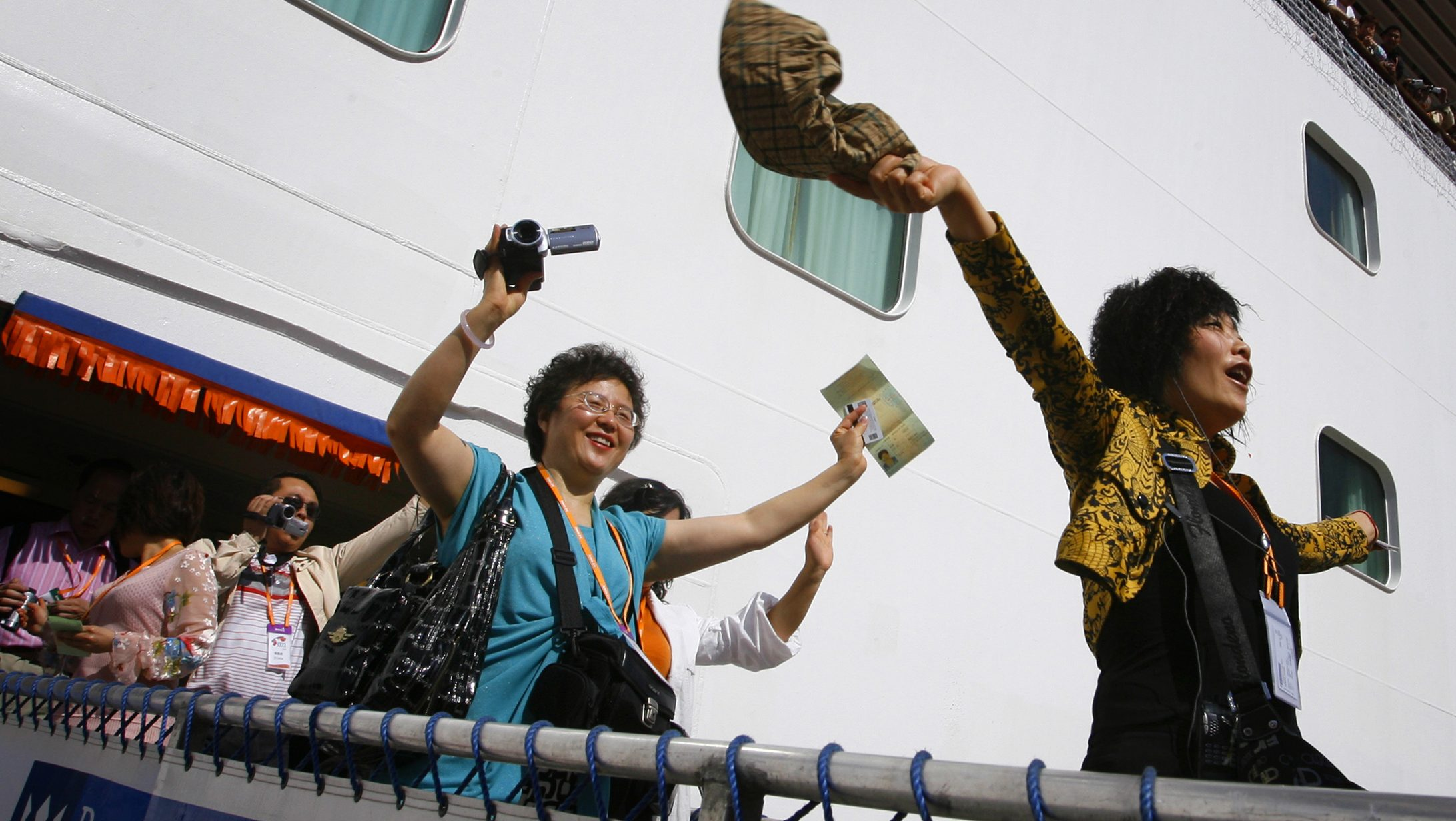 Tourists from China wave as they arrive on a cruise ship in the northern Taiwan port of Keelung March 16, 2009. A total of 1,600 employees from Amway China arrived on Monday, the first large-scale tour group from the mainland via a foreign-owned cruise ship since the opening of direct transport links from the mainland last year. REUTERS/Nicky Loh (TAIWAN POLITICS TRAVEL BUSINESS IMAGE OF THE DAY TOP PICTURE) - RTXCU5A