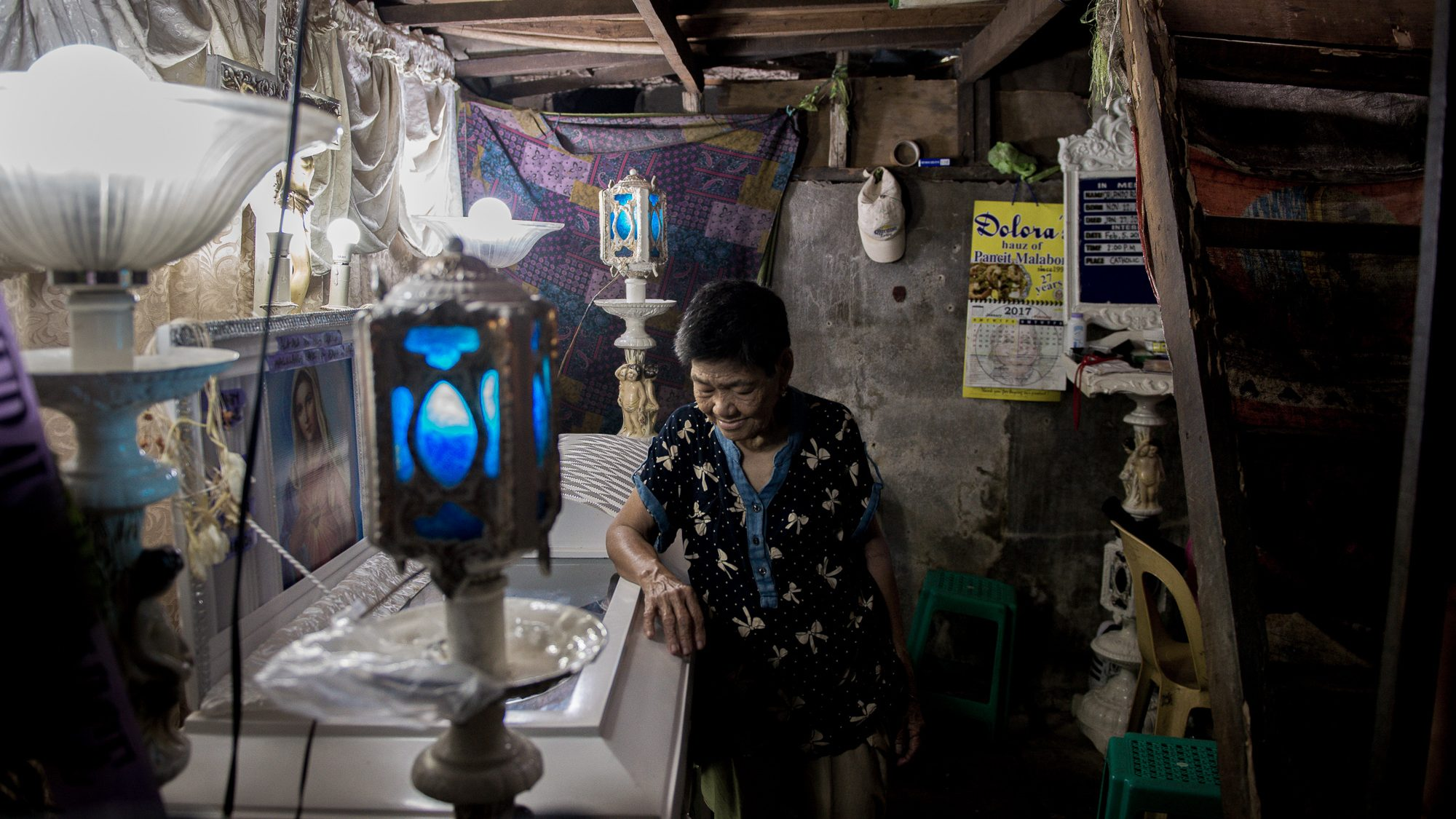 Irenea Fernando, 73, mother of Orlando Bernardo, looks over her son's casket in their shanty home in Navotas, north of Manila. Bernardo was found dead on a nearby road, a day after he went missing.