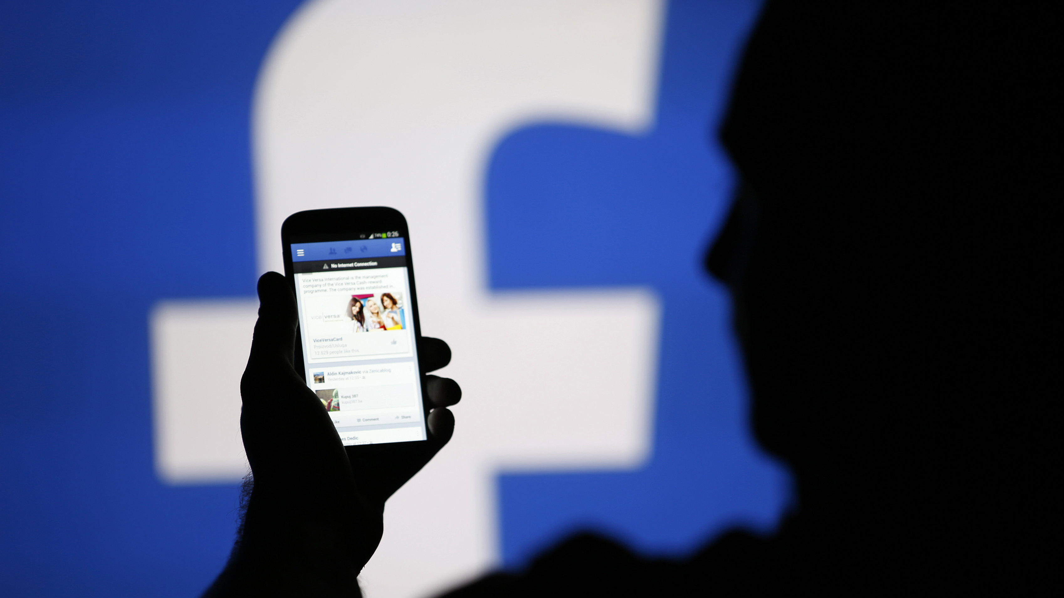 A man is silhouetted against a video screen with an Facebook logo as he poses with an Samsung S4 smartphone in this photo illustration taken in the central Bosnian town of Zenica