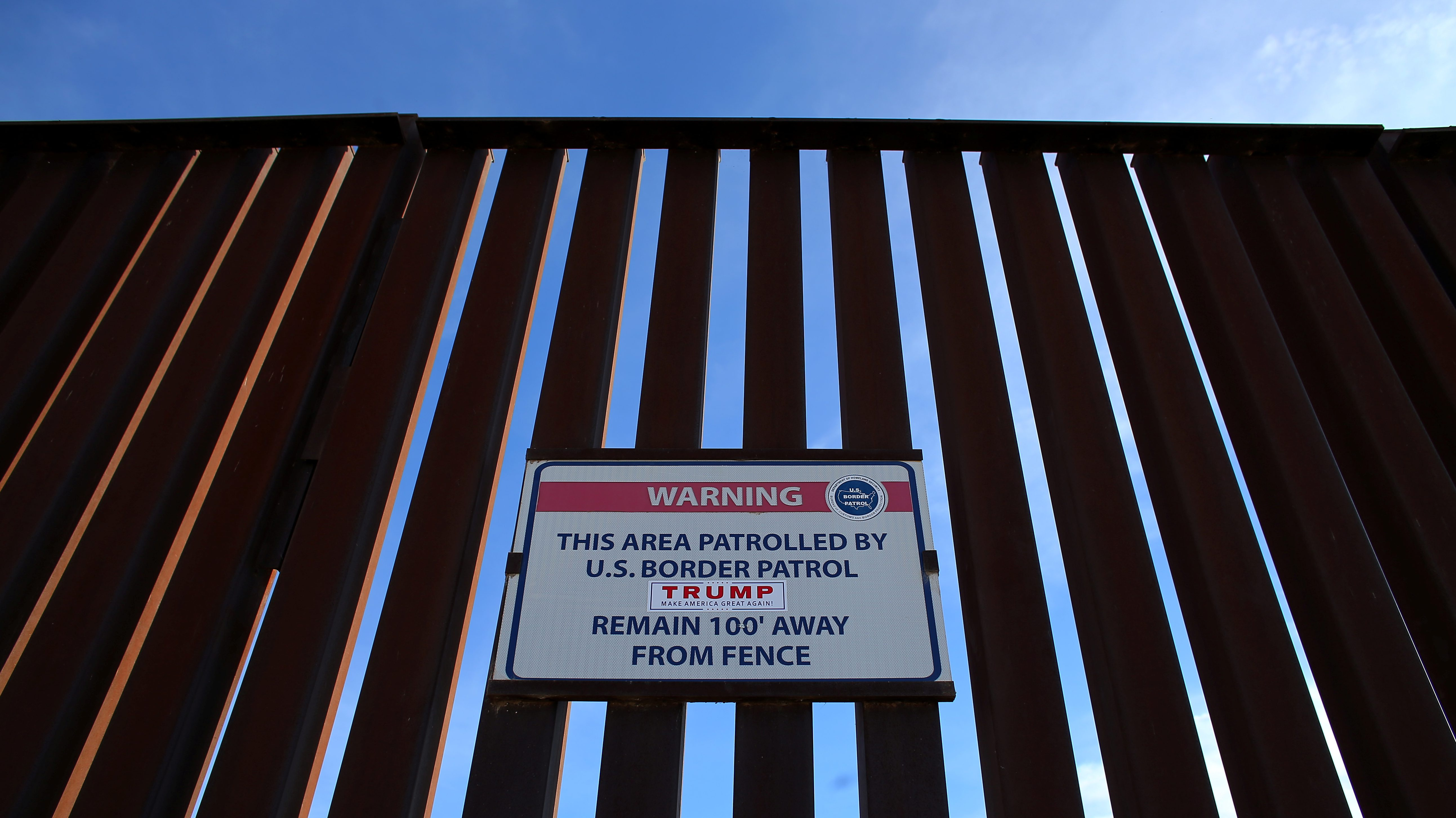 A Donald Trump for President campaign sticker is shown attached to a U.S. Customs sign hanging on the border fence between Mexico and the United States