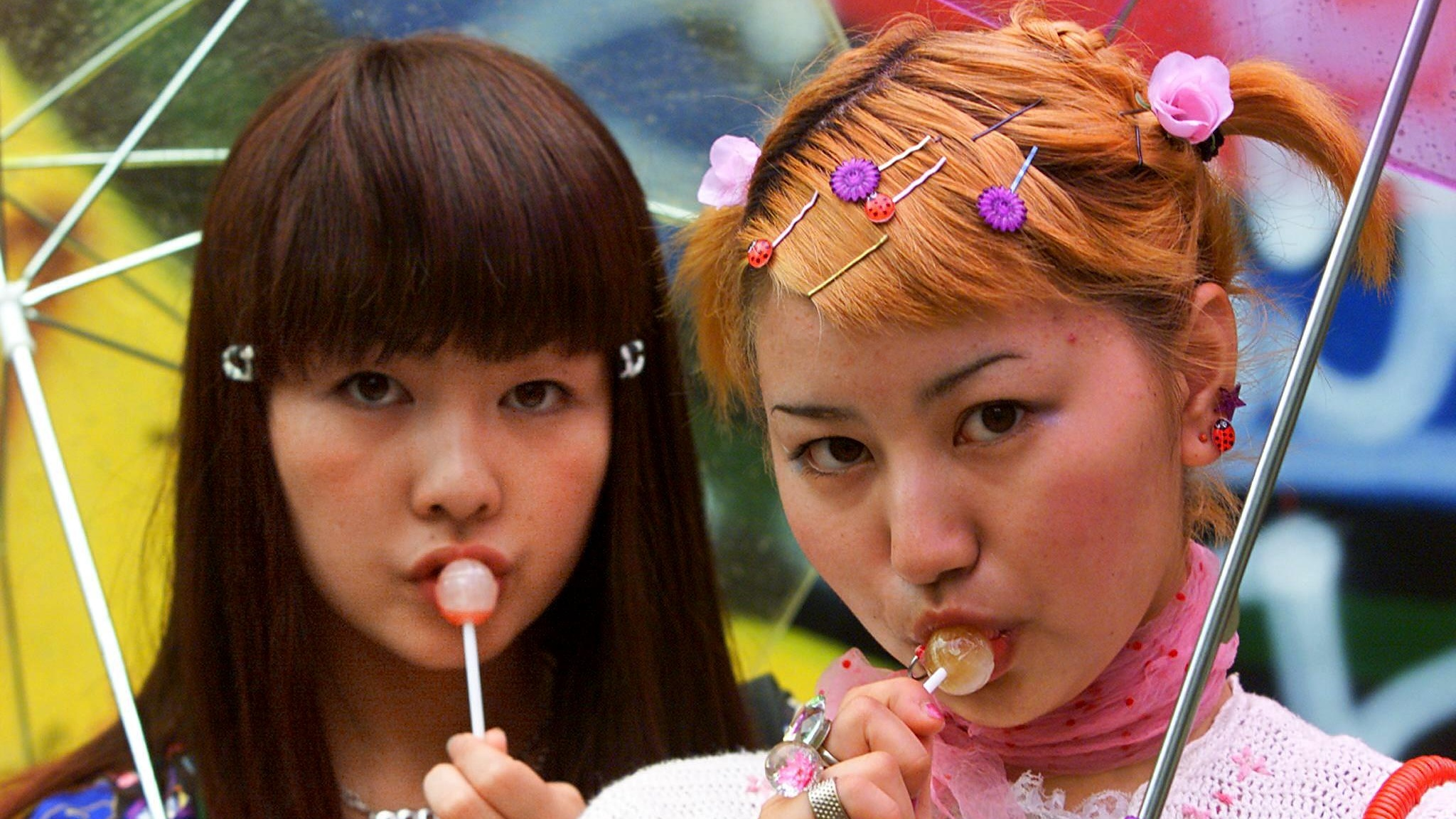 """TOKYO, JAPAN:  Eighteen-year-old student Yoko Sasaki (R) and her classmate Anna Shimasaki (L) pose for pictures on a street at Tokyo fashion district Harajuku, 17 June 2000.  Fashion conscious Japanese girls, referred to as """"kogyaru"""" in Japanese, often shape the future of fashion with their shopping patterns and dressing styles.      (ELECTRONIC IMAGE)   AFP PHOTO/Toru YAMANAKA (Photo credit should read TORU YAMANAKA/AFP/Getty Images)"""