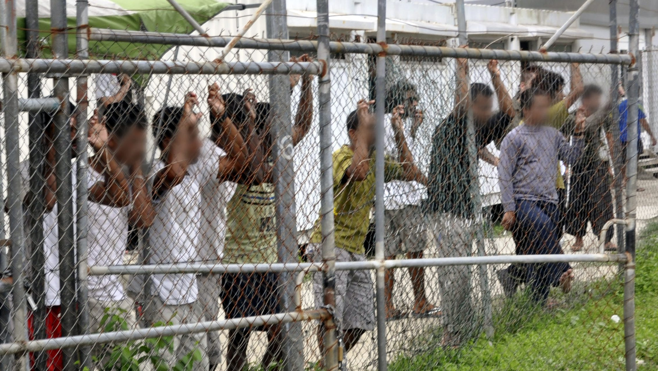 epa05279193 A picture dated 21 March 2014 and made available on 27 April 2016 shows asylum seekers staring at media from behind a fence at the Oscar compound in the Manus Island detention center, Papua New Guinea. Papua New Guinea (PNG) Prime Minister Peter O'Neill said on 27 April 2016, that Australia's Manus Island detention center will be closes following a decision by the PNG Supreme Court declaring it as unconstitutional. According to reports, O'Neil urged the Australian government to seek alternative arrangements for asylum seekers.  EPA/EOIN BLACKWELL -- BEST QUALITY AVAILABLE -- ATTENTION EDITORS: PICTURE PIXELATED AT SOURCE -- AUSTRALIA AND NEW ZEALAND OUT