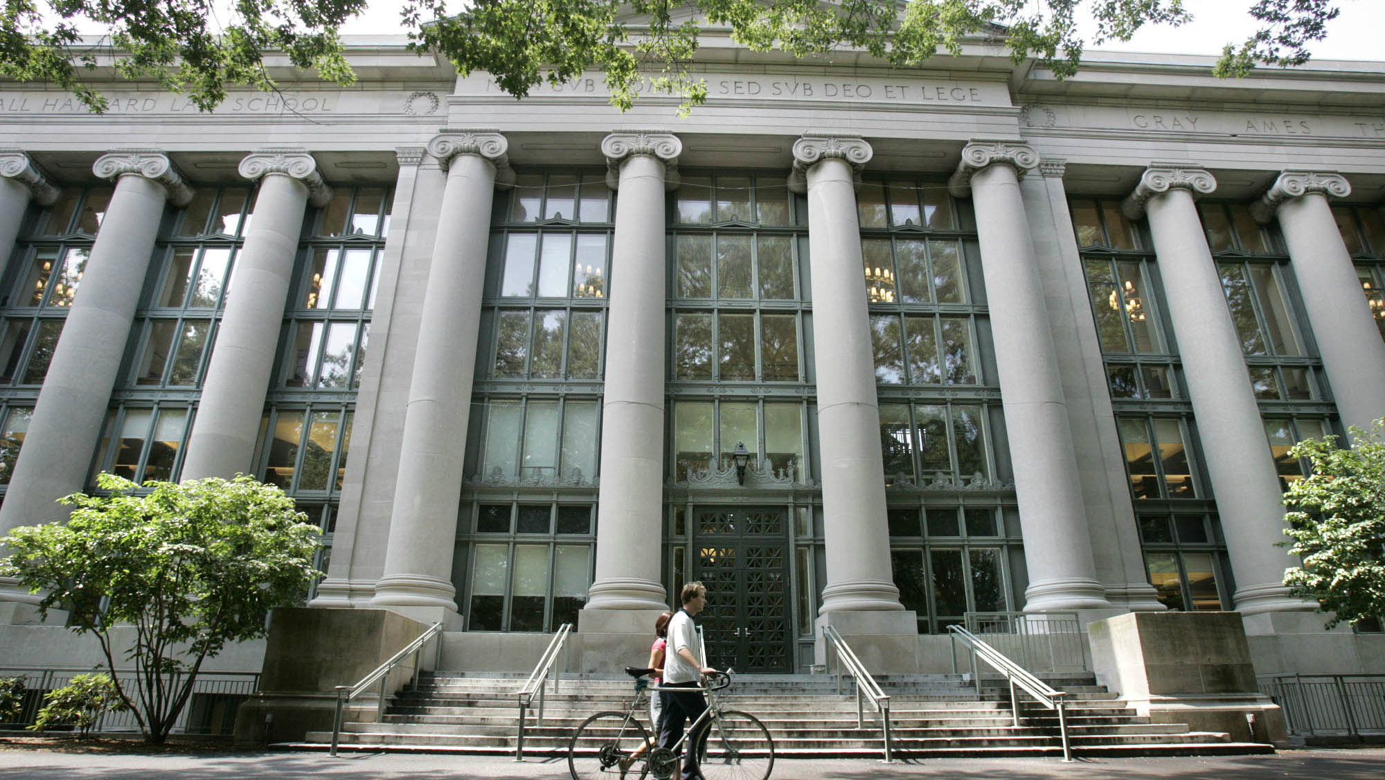 In this Aug. 1, 2005 file photo, a bicyclist walks by Langdell Hall, the Harvard Law Library, on the Harvard Law School campus at Harvard University in Cambridge, Mass. Some students at Harvard Law School want it to change its official seal because of its ties to an 18th-century slaveholder. The seal depicts three bundles of wheat, an image taken from the family crest of Isaac Royall Jr. It's meant to pay tribute to Royall, who left his estate to create the first law professorship at Harvard University but who was a slave trader and owned slaves at his Massachusetts home.