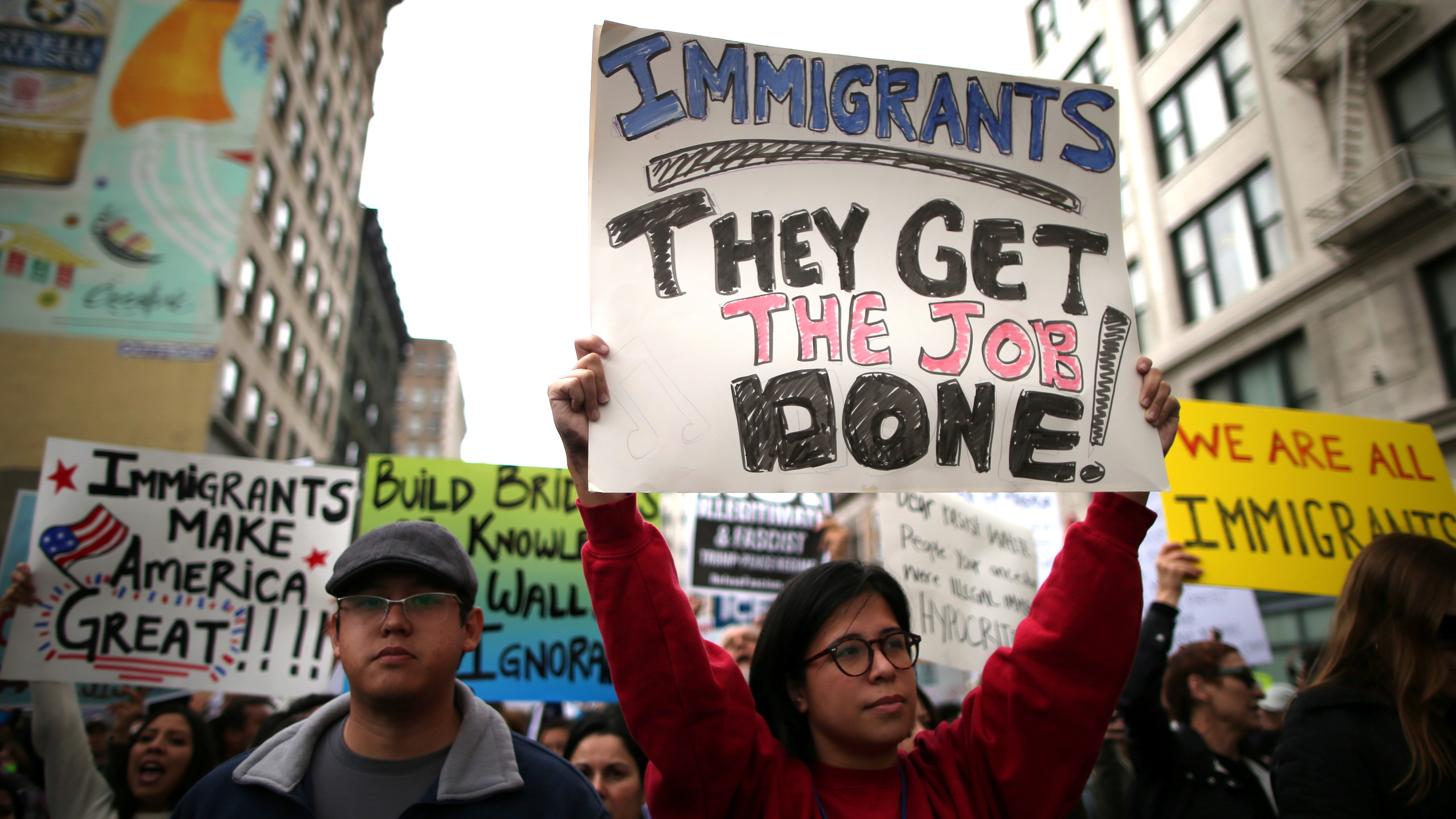 People participate in a protest march calling for human rights and dignity for immigrants