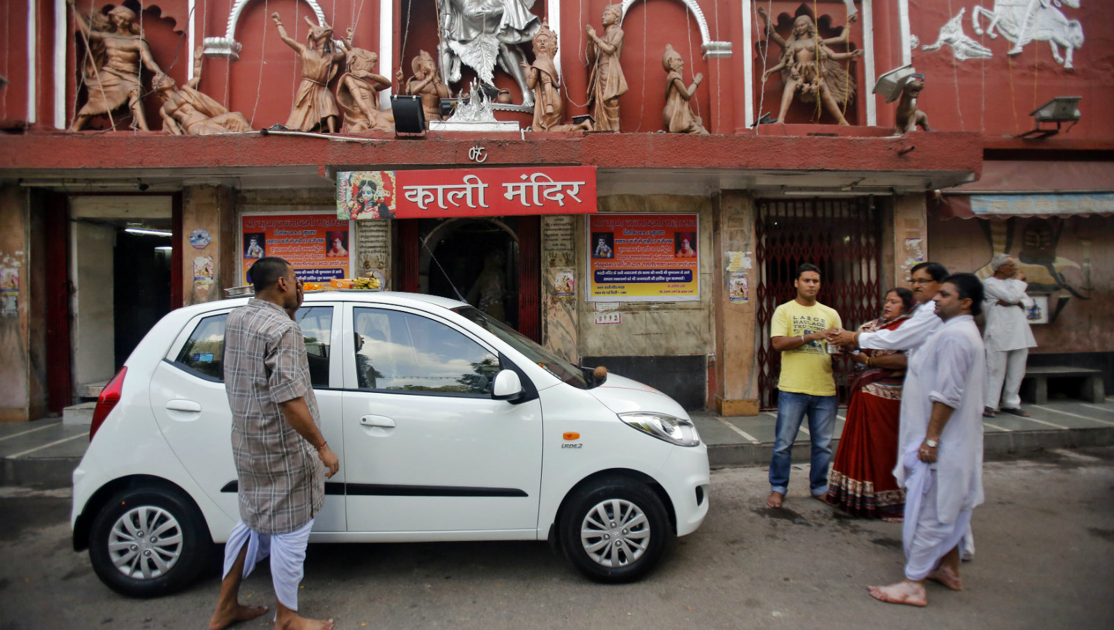 A Hindu priest (2nd R) blesses a new car with its owners outside a temple in New Delhi September 2, 2013. The Indian auto sector is down 7.9 percent for the year to date, compared to an average 20.7 percent climb for global auto stocks.