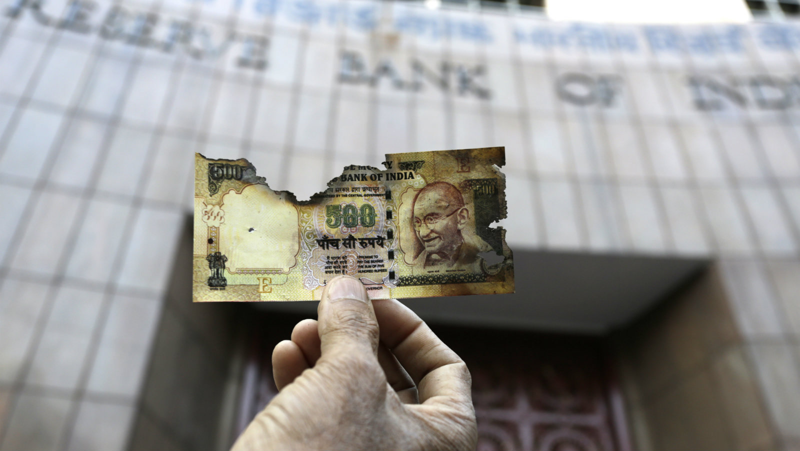 A man holds a charred facsimile of the discontinued Indian currency 500 note after a protest by a traders association demanding adequate arrangement to exchange discontinued currency notes outside Reserve Bank of India in Kolkata, India, Wednesday, Nov. 16, 2016. India announced a week ago that it was withdrawing 500 and 1,000 rupee notes as legal tender to fight corruption and tax evasion. However, people are allowed a onetime swap of 4,000 rupees ($59) at any bank in exchange for smaller notes to meet immediate needs.