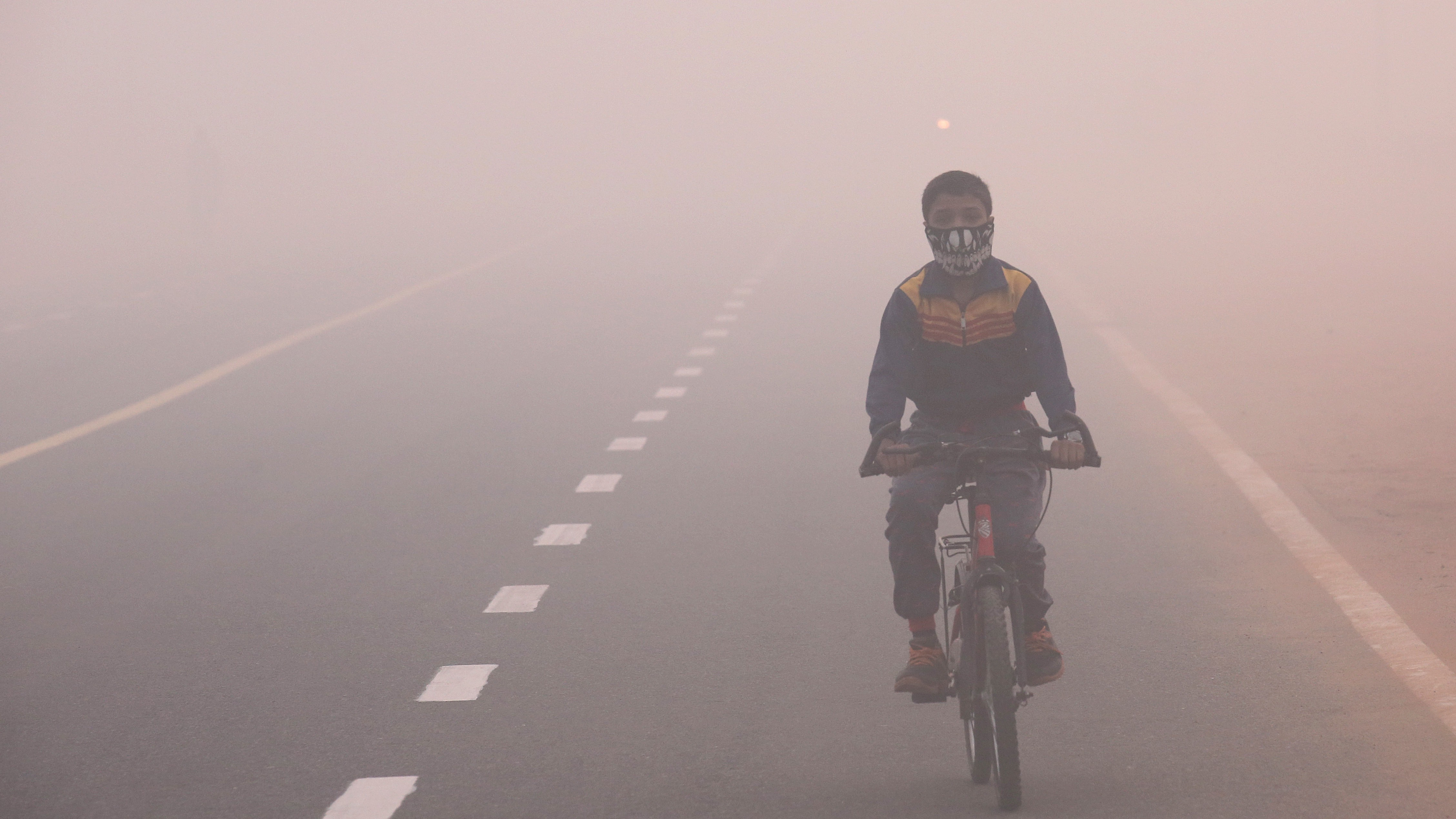 An Indian child wearing a face mask cycles in smog, one day after the Diwali festival, in New Delhi, India, 31 October 2016. According to a news report, hundreds of people faced breathing problem and poor visibility due to heavy smog after fireworks set off during the Diwali festival in Delhi have worsened the pollution problem.