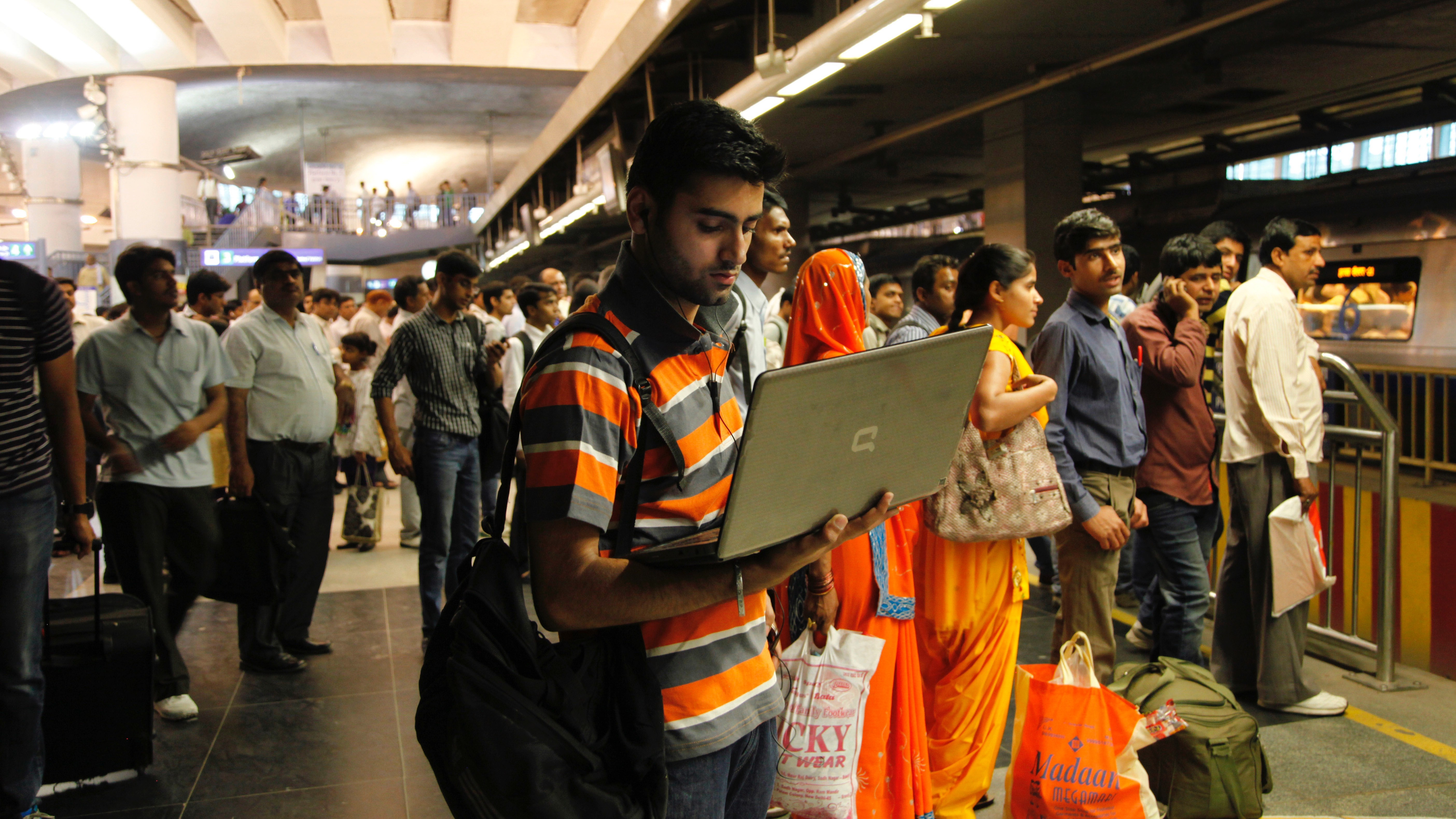 An Indian man works on his laptop as he stands at a metro station in New Delhi, India, Friday, April 4, 2014. In a few decades, India has gone from a country mostly concerned with securing food, clothing and shelter to one in which the priorities are now jobs, electricity and infrastructure. Those gaps are even more visible with the technology explosion. While ten years ago most people had never seen a television or a mobile phone, today there are more than 200 TV channels, with some 40 devoted to news alone, while three in four Indians has a cell phone. (AP Photo/Tsering Topgyal)