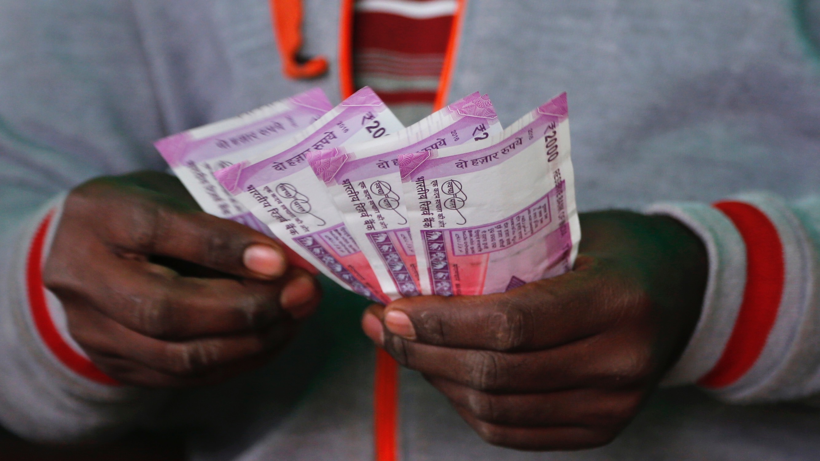 A trader counts new 2,000-rupee notes at a wholesale vegetable market in Bangalore, India, Friday, Dec. 30, 2016. India yanked most of its currency bills from circulation without warning, delivering a jolt to the country's high-performing economy and leaving countless citizens scrambling for cash. Still, as Friday's deadline for depositing old 500- and 1,000-rupee notes draws to a close, Prime Minister Narendra Modi's government has called the demonetization drive a great success in drawing out tax dodgers and eliminating graft. (AP Photo/Aijaz Rahi)
