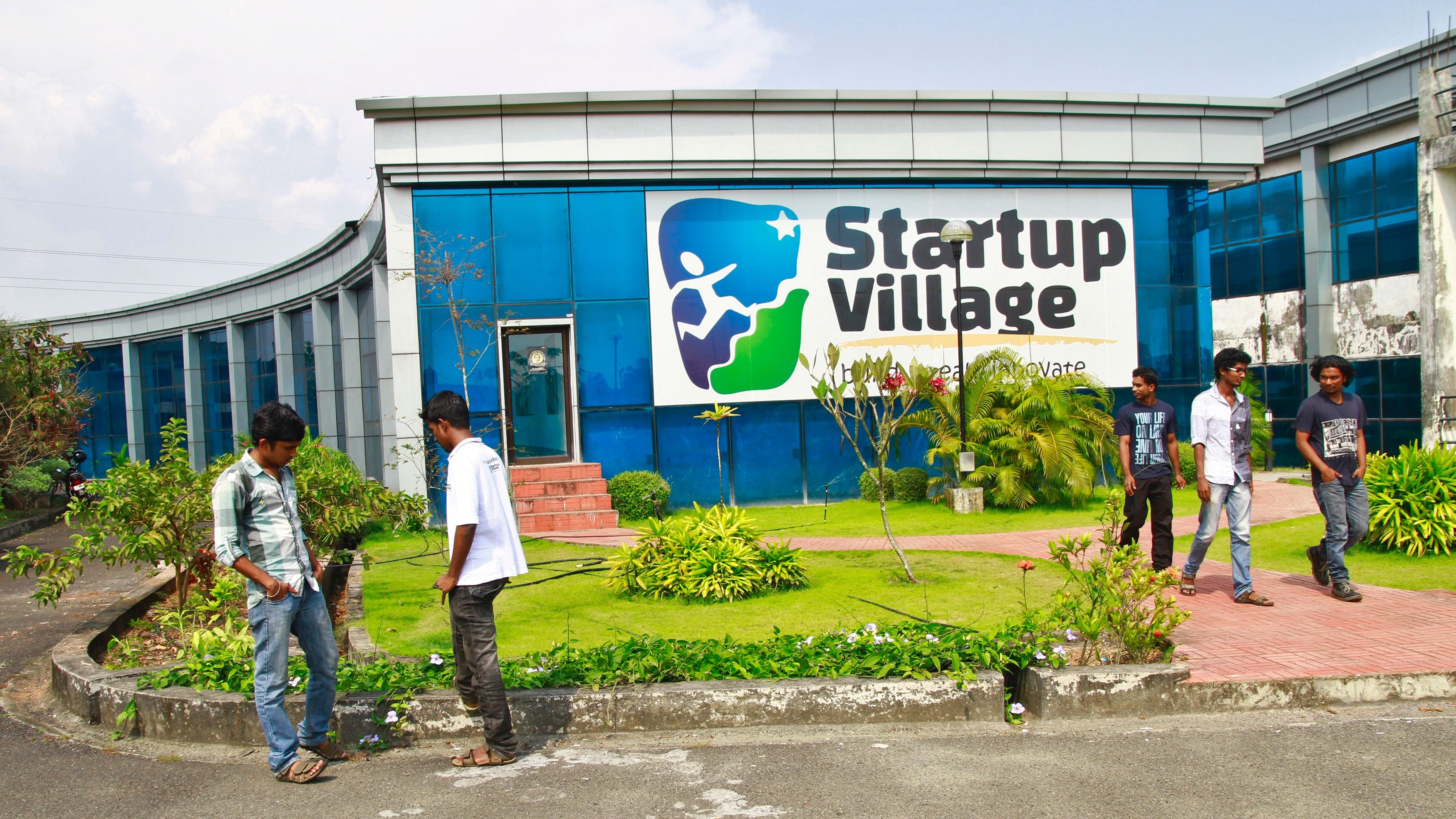 Employees stand outside the Start-up Village in Kinfra High Tech Park in the southern Indian city of Kochi October 13, 2012. Three decades after Infosys, India's second-largest software service provider, was founded by middle-class engineers, the country has failed to create an enabling environment for first-generation entrepreneurs. Startup Village wants to break the logjam by helping engineers develop 1,000 Internet and mobile companies in the next 10 years. It provides its members with office space, guidance and a chance to hobnob with the stars of the tech industry. But critics say this may not even be the beginning of a game-changer unless India deals with a host of other impediments - from red tape to a lack of innovation and a dearth of investors - that are blocking entrepreneurship in Asia's third-largest economy. To match Feature INDIA-TECHVILLAGE/ Picture taken October 13, 2012. REUTERS/Sivaram V (INDIA - Tags: BUSINESS SCIENCE TECHNOLOGY EMPLOYMENT) - RTR3B6E0
