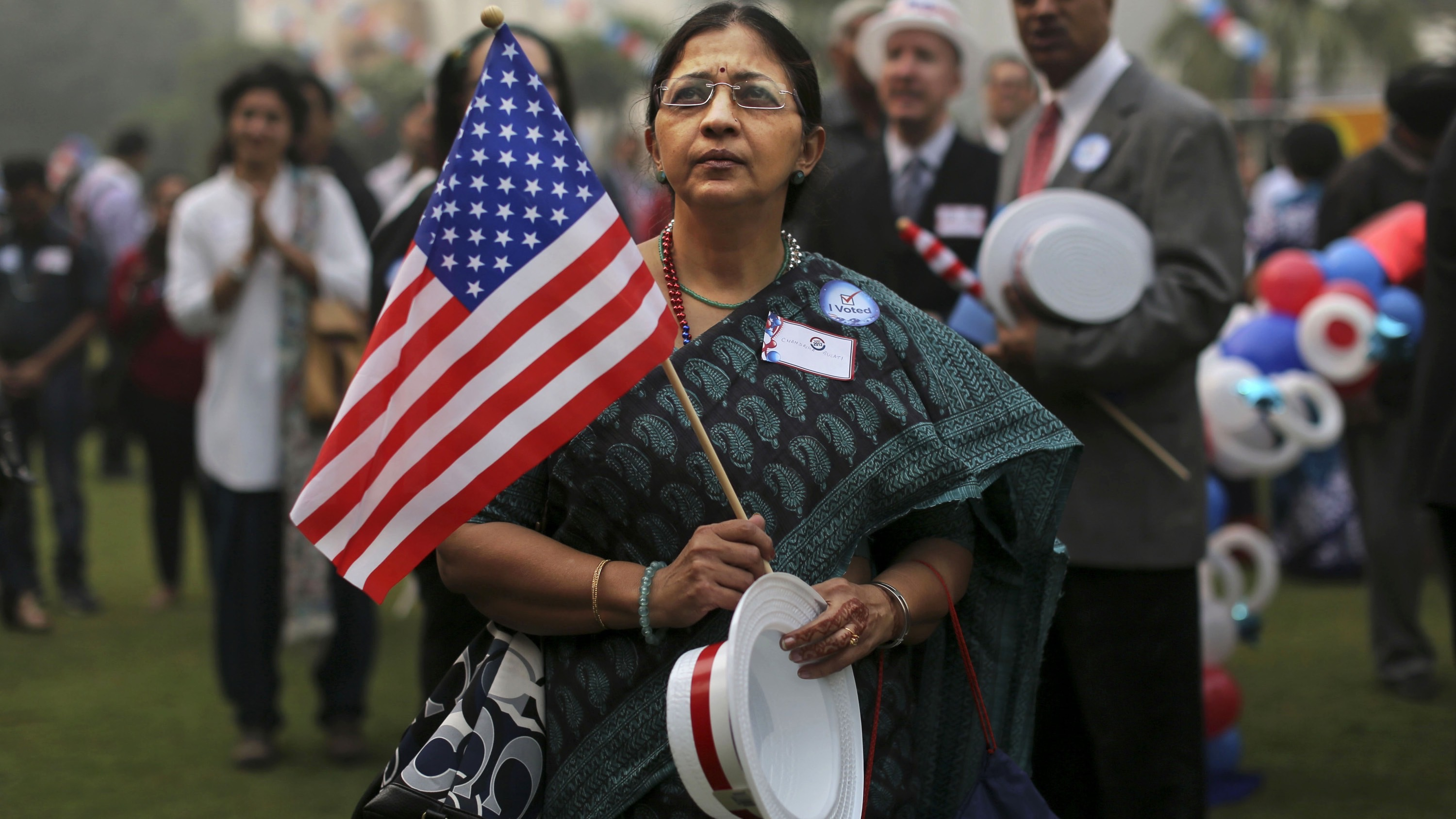 A woman wearing a sari watches during an event organized by the U.S embassy to mark the Presidential elections at the landmark Imperial Hotel in New Delhi, India, Wednesday, Nov. 7, 2012. Obama captured a second White House term, blunting a mighty challenge by Republican Mitt Romney as Americans voted for a leader they knew over a wealthy businessman they did not. (AP Photo/Kevin Frayer)