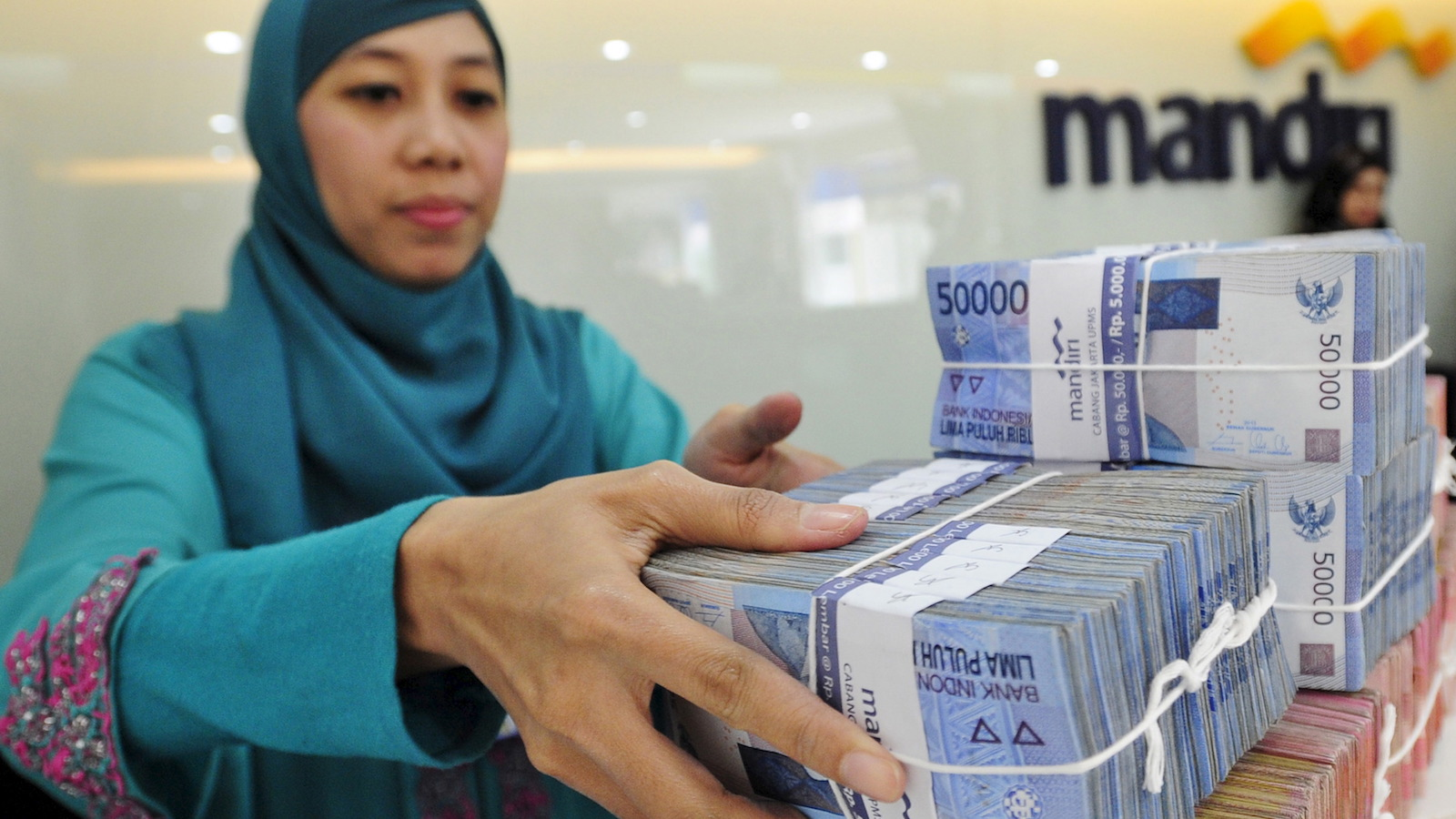 A teller at a Bank Mandiri branch handles Indonesian Rupiah currency during a transaction in Jakarta July 20, 2015 in this photo taken by Antara Foto.  The Indonesian rupiah hit a fresh 17-year low on July 23, 2015, as solid U.S. housing data added to expectations the Federal Reserve with hike interest rates as soon as September. Picture taken July 20, 2015. REUTERS/Wahyu Putro A/Antara Foto ATTENTION EDITORS - THIS IMAGE HAS BEEN SUPPLIED BY A THIRD PARTY. IT IS DISTRIBUTED, EXACTLY AS RECEIVED BY REUTERS, AS A SERVICE TO CLIENTS. FOR EDITORIAL USE ONLY. NOT FOR SALE FOR MARKETING OR ADVERTISING CAMPAIGNS MANDATORY CREDIT. INDONESIA OUT. NO COMMERCIAL OR EDITORIAL SALES IN INDONESIA. - RTX1LFNO