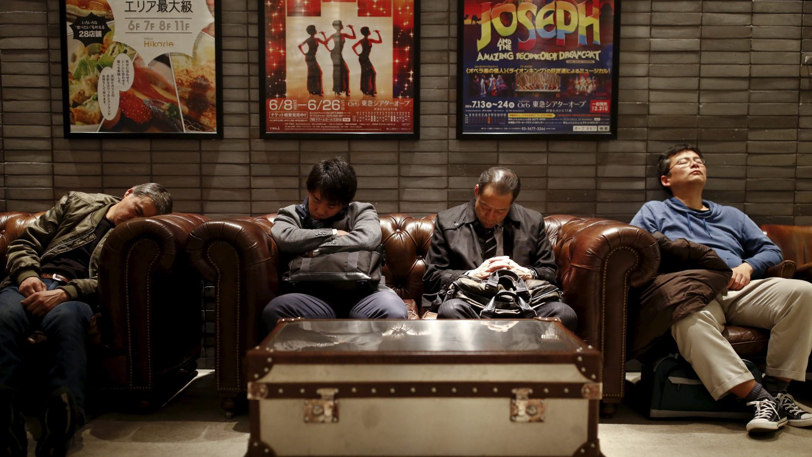 Men sleep in couches in a public seating area in a department store in Tokyo, Japan, March 17, 2016. REUTERS/Thomas Peter - RTSATRA