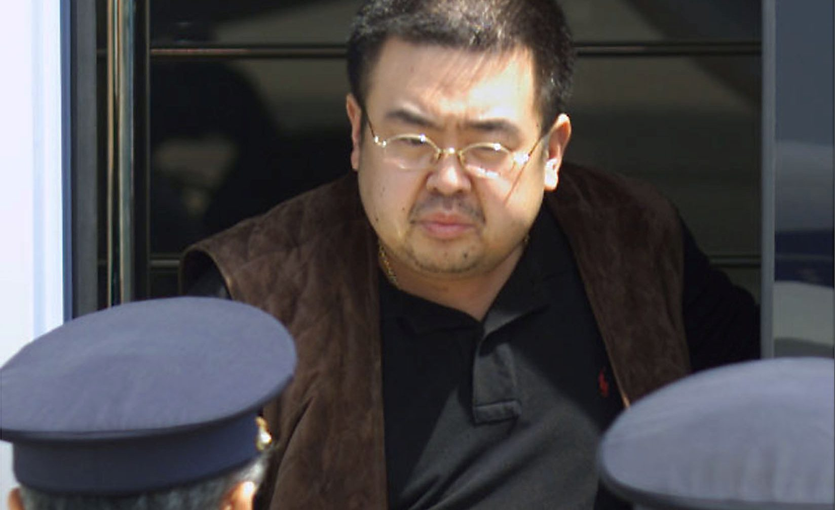 A man believed to be North Korean heir-apparent Kim Jong Nam emerges from a bus as he is escorted by Japanese authorities upon his deportation from Japan at Tokyo's Narita international airport