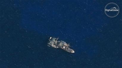 A refrigerated cargo vessel meeting with two fishing vessels in the Indian Ocean.