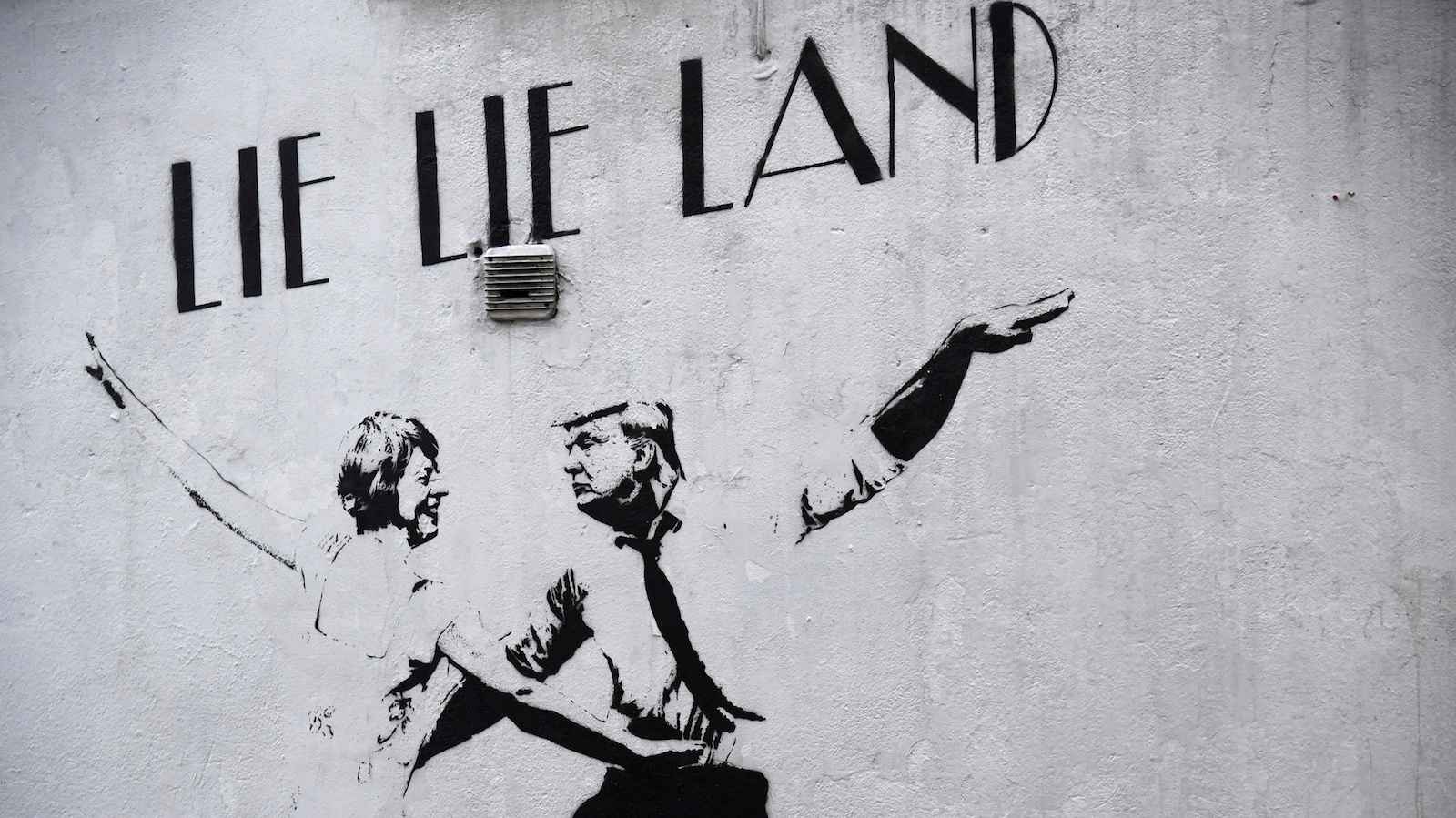 "A mural depicting U.S. President Trump dancing with British Prime Minister May, painted in a style similar to the cinema poster for the film musical ""La La Land"" is seen on a wall in London"