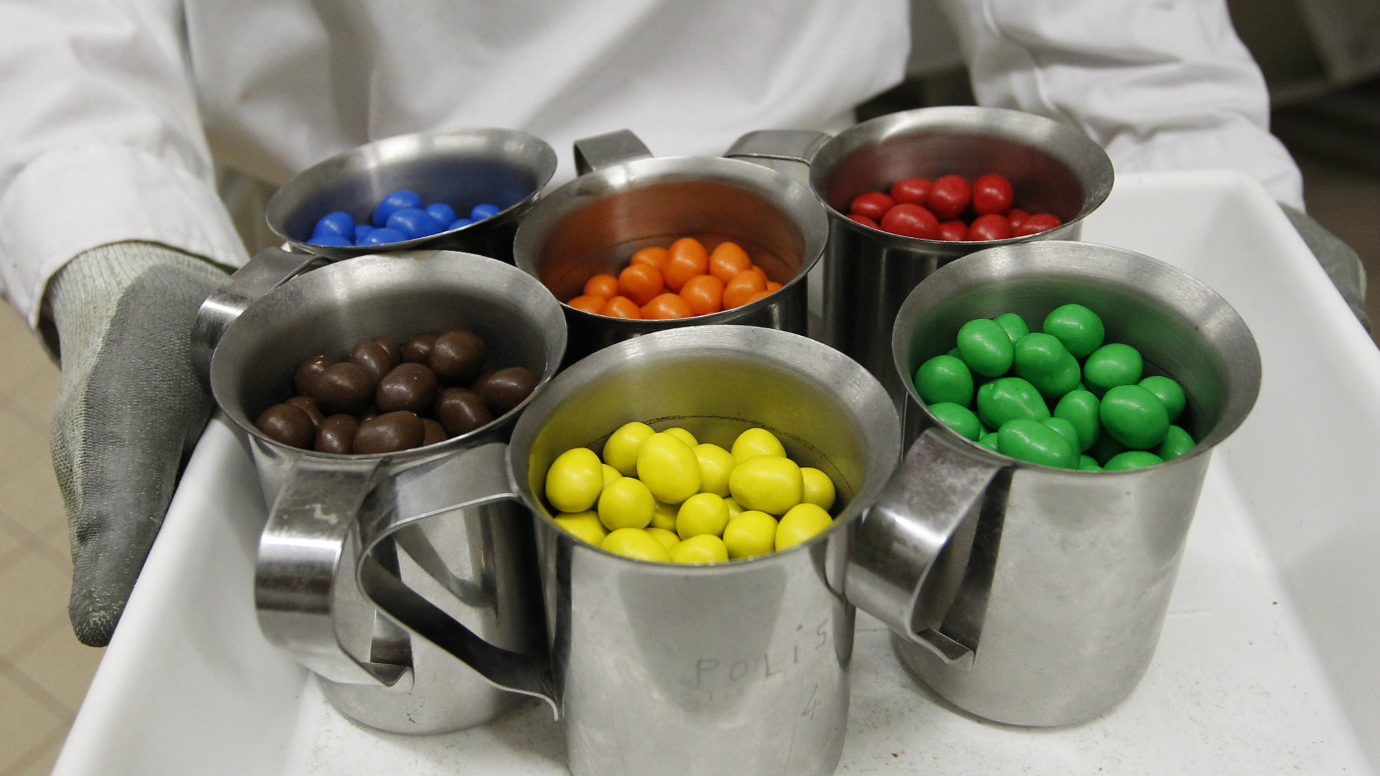 An employee holds a tray of different-coloured M&M's candies at the production line of candy and chocolate maker Mars Chocolate France's plant in Haguenau, eastern France, December 13, 2011.
