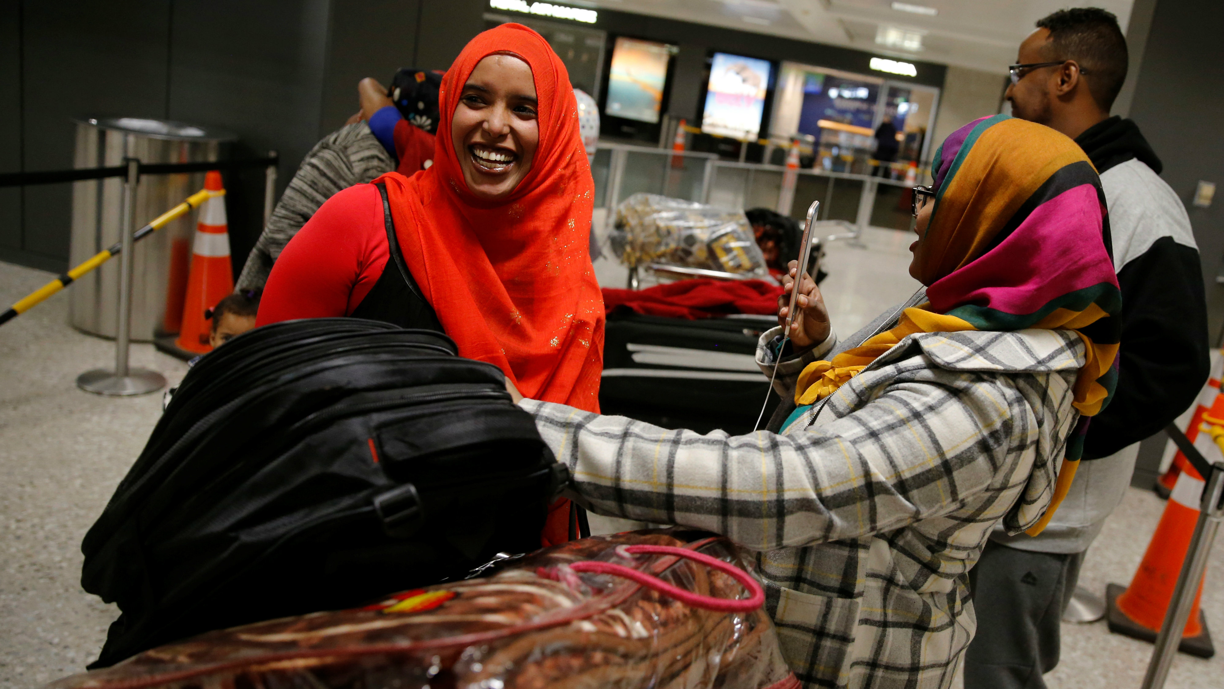 Najmia Abdishakur (L), a Somali national who was delayed entry to the U.S. because of the recent travel ban, smiles as her family welcomes her at Washington Dulles International Airport in Chantilly, Virginia, U.S. February 6, 2017.