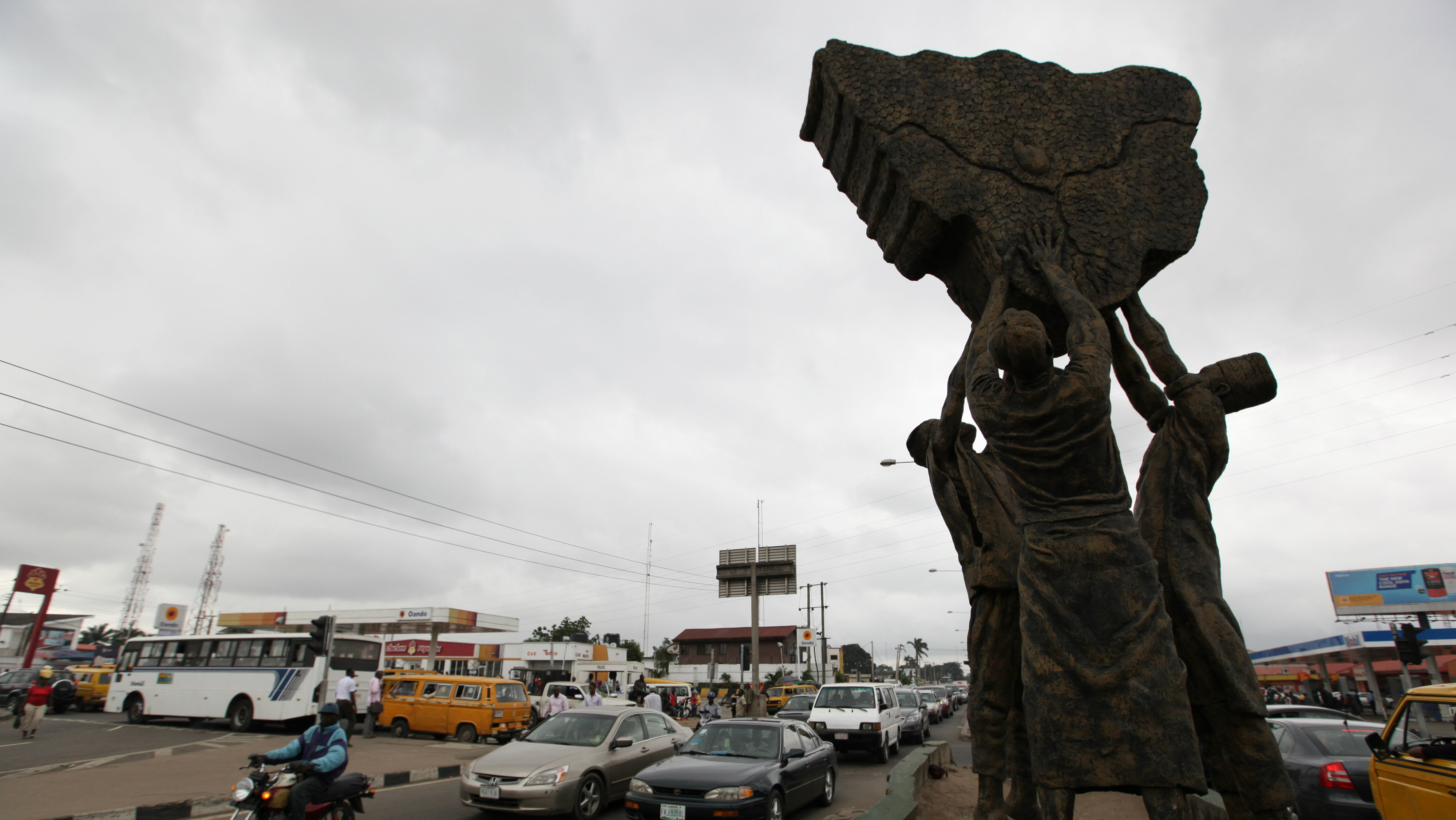 Traffic passes a statue depicting Nigeria's three major tribes, the Hausa, the Igbo and the Yoruba, lifting up a map depicting Nigeria in Lagos, Nigeria, on Wednesday, Sept. 5, 2012