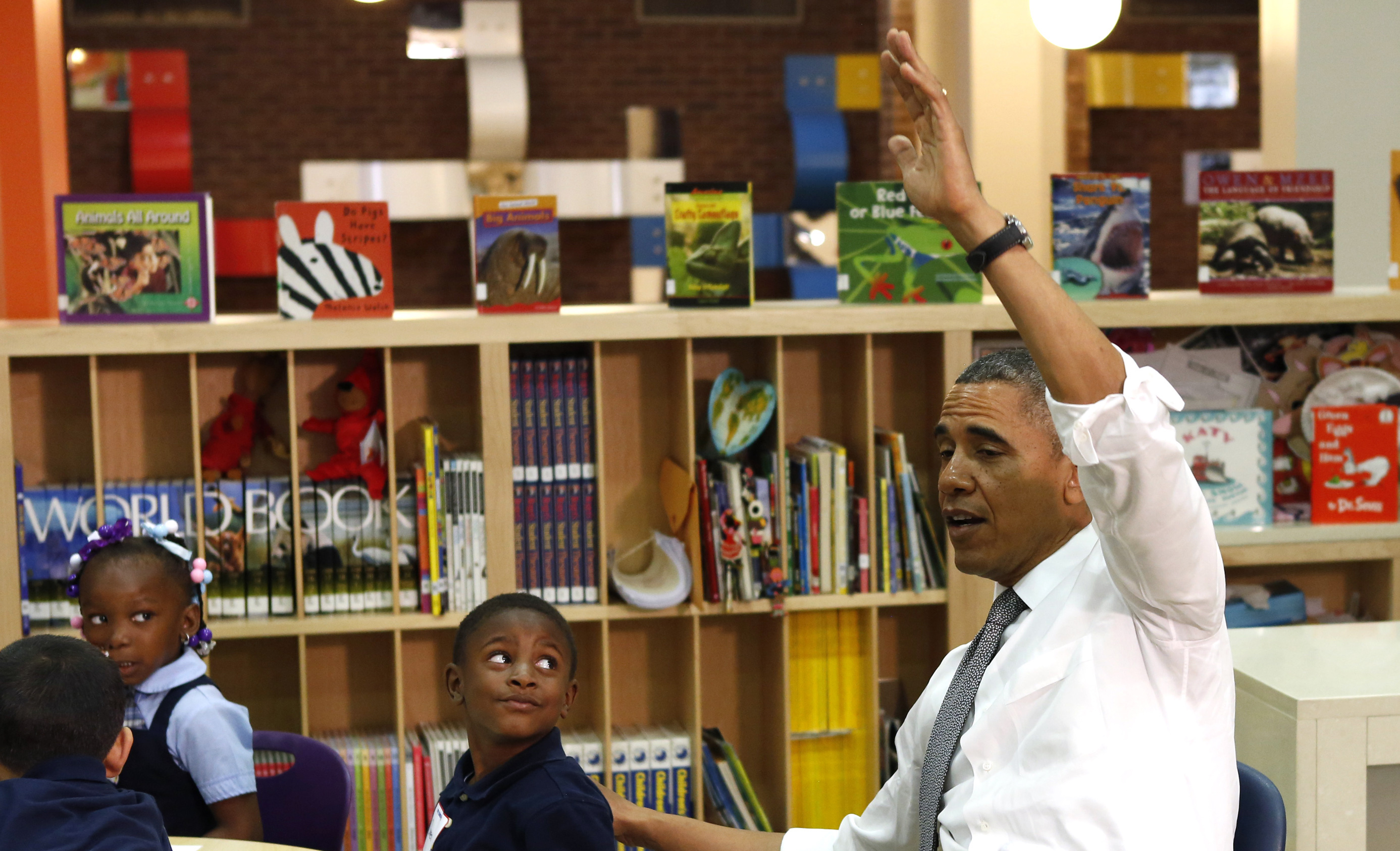 Obama raising his hand in a classroom with students.