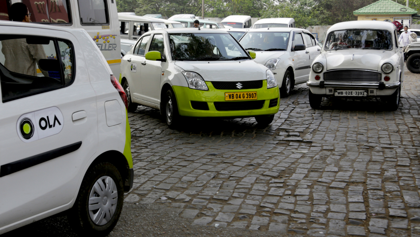 In this March 29, 2016 photo, Ola cabs, left, waiting for customers are parked next to other cars in Kolkata, India. Aiming to wrest control of India's booming taxi market, two cab-hailing smartphone apps, Uber and Ola, are promising hundreds of millions in new investments while also facing off with one another in court.