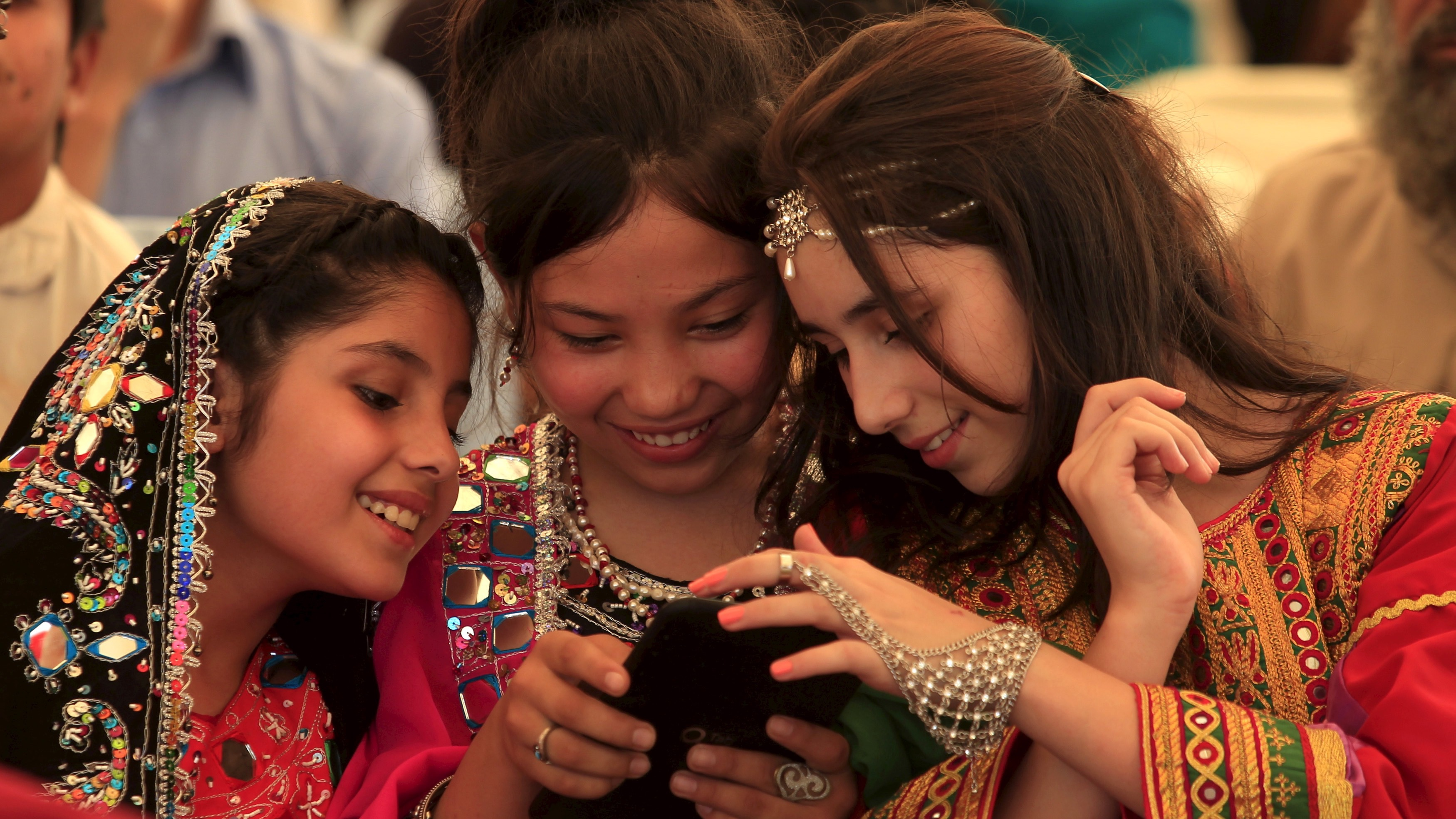 Afghan refugee girls wearing traditional dresses play with a mobile phone while watching a friendly cricket match between Pakistani students and a team from the Afghanistan Embassy during an event on the eve of Afghan Refugee Day in Islamabad, Pakistan, June 16, 2015. REUTERS/Faisal Mahmood   - RTX1GQXA