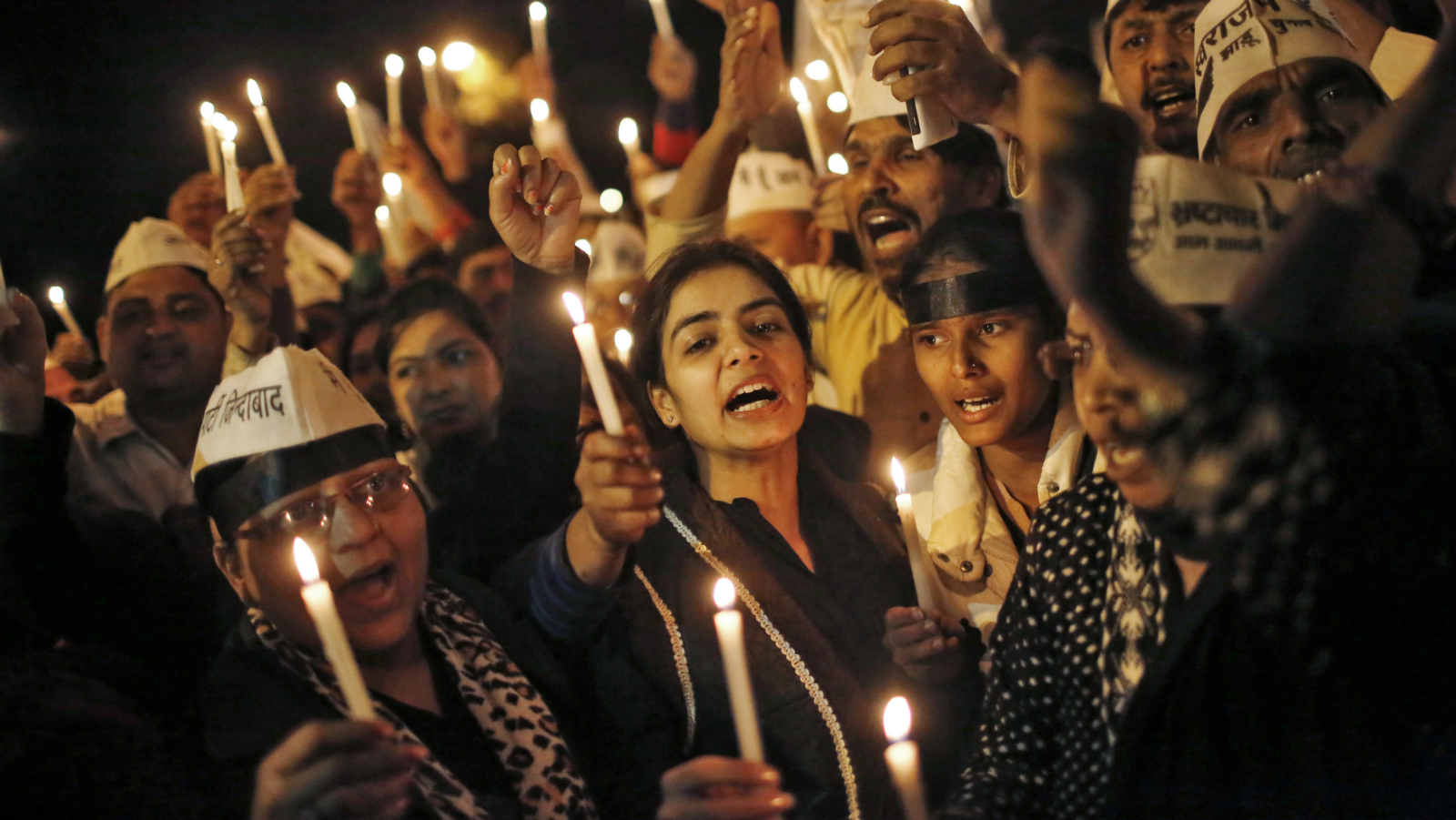 Supporters of Aam Aadmi (Common Man) Party (AAP) shout slogans as they participate in a candle light vigil during a protest against the rape of a female passenger, in New Delhi December 8, 2014. U.S. online ride-hailing service Uber has been banned from operating in the Indian capital after a female passenger accused one of its drivers of rape, a case that has reignited a debate about the safety of women in the South Asian nation.