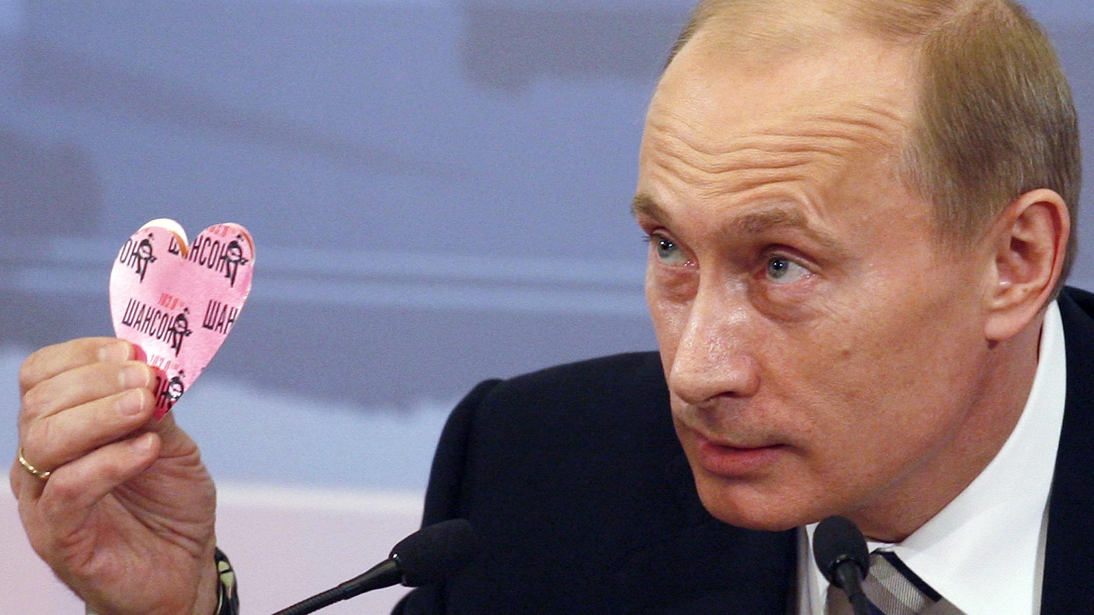 Russia's President Vladimir Putin holds up a heart.
