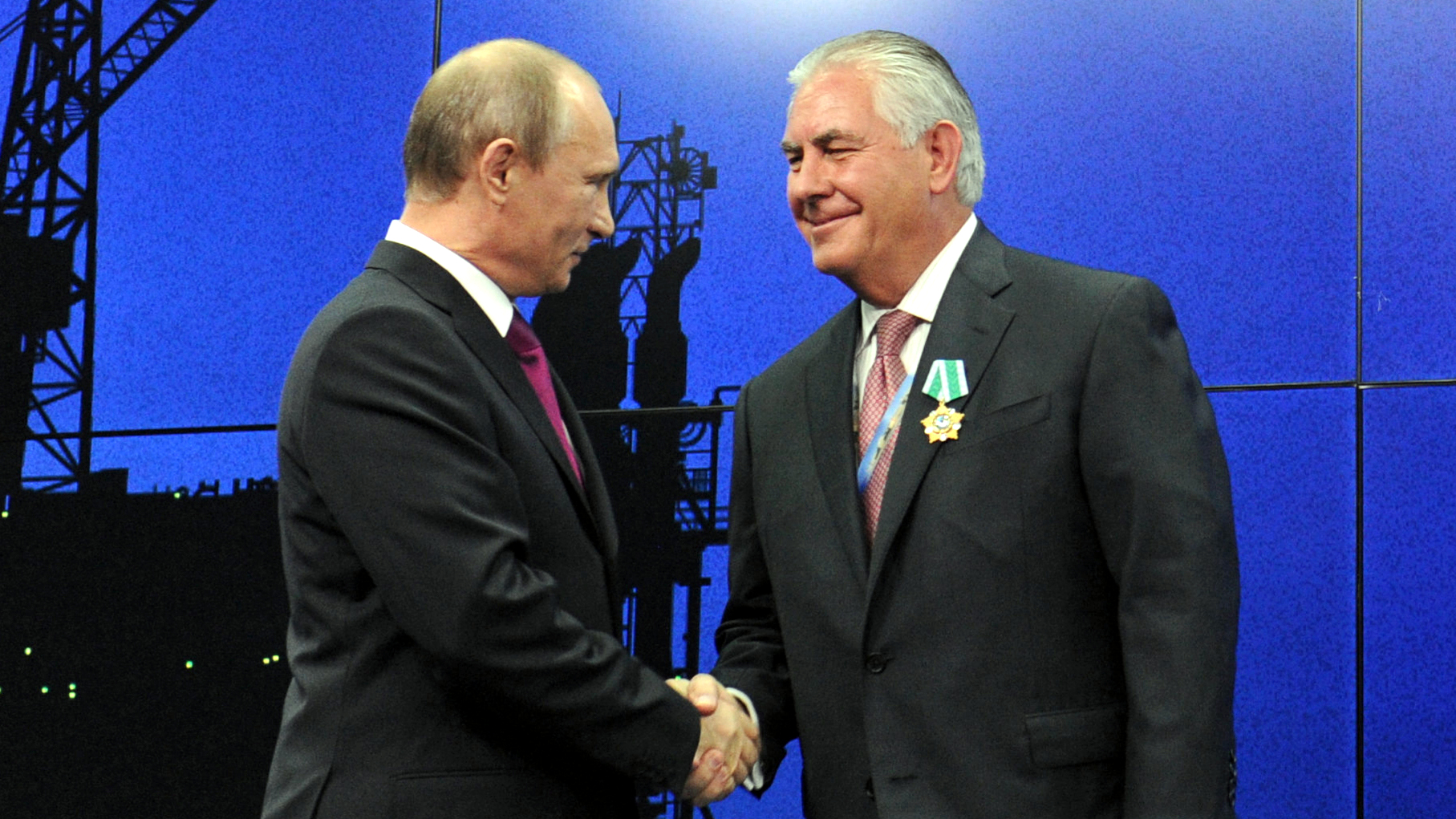 In this photo taken Thursday, June 21, 2012, Russian President Vladimir Putin presents ExxonMobil CEO Rex Tillerson with a Russian medal at an award ceremony of heads and employees of energy companies at the St. Petersburg economic forum in St. Petersburg, Russia.  (