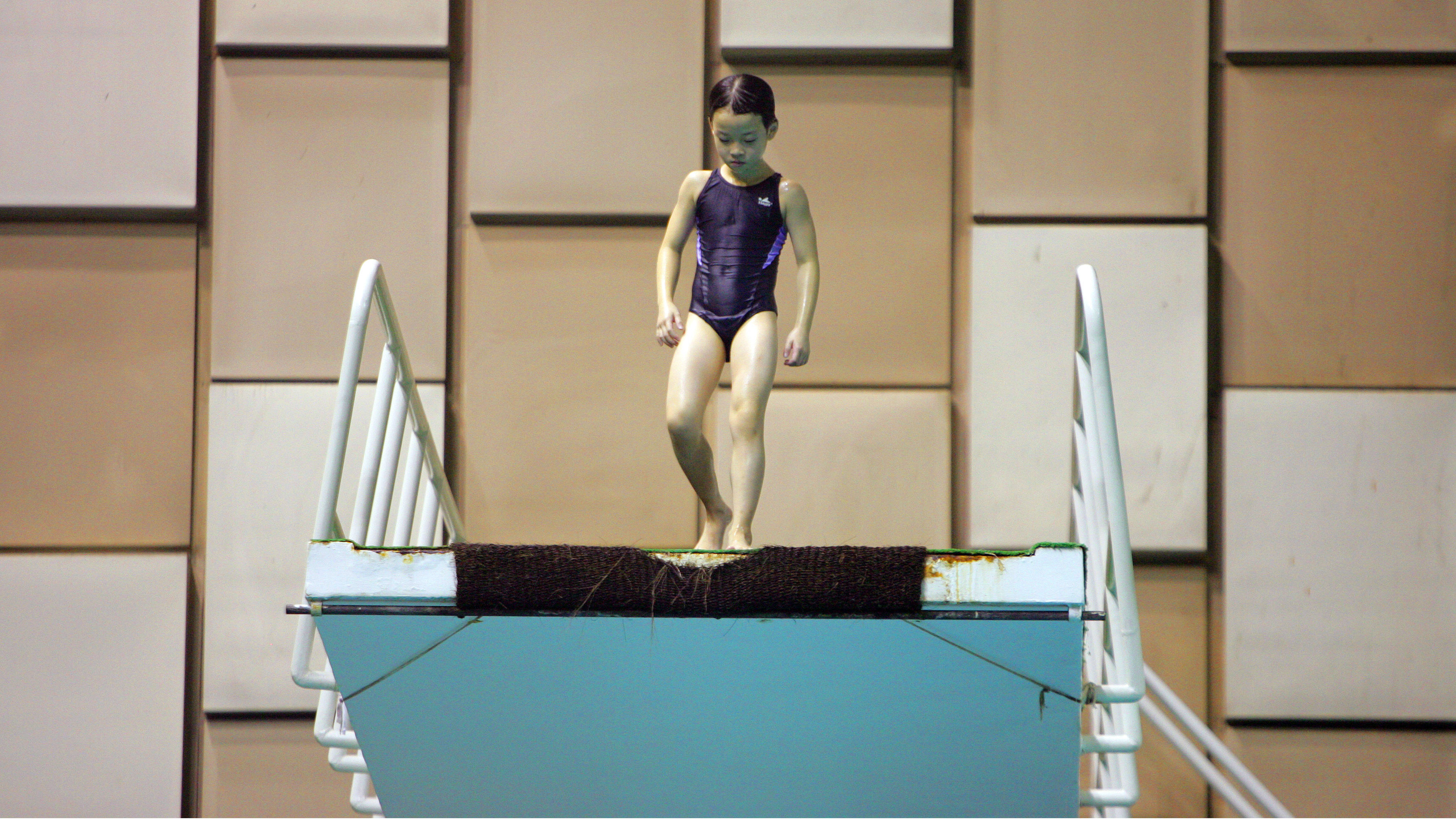 Girl waits at platform to dive into swimming pool at athlete training school in Shanghai