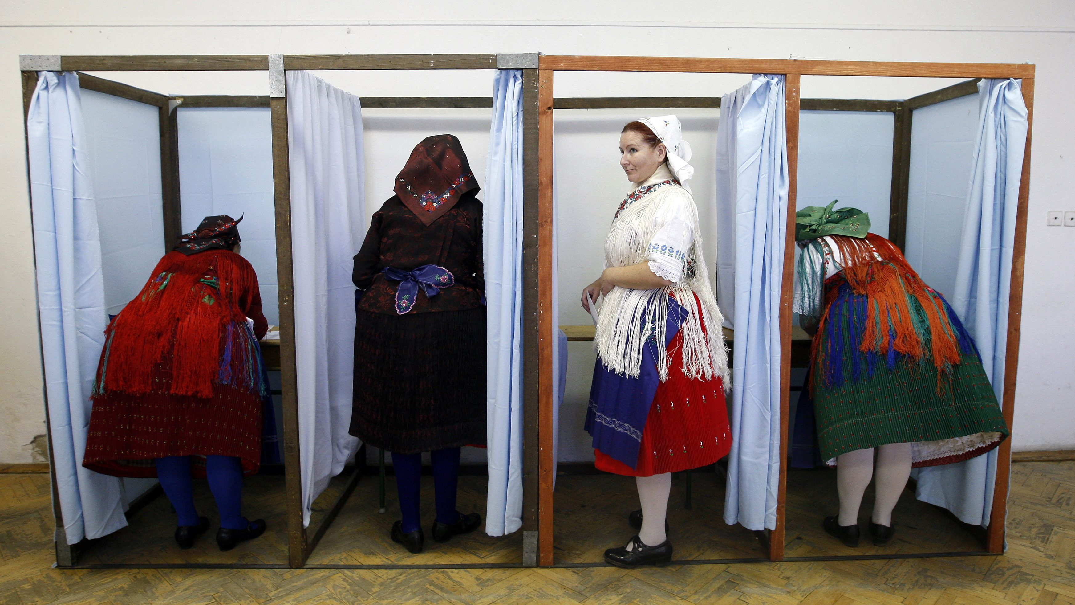 Hungarian women wearing traditional costumes fill in their ballot papers